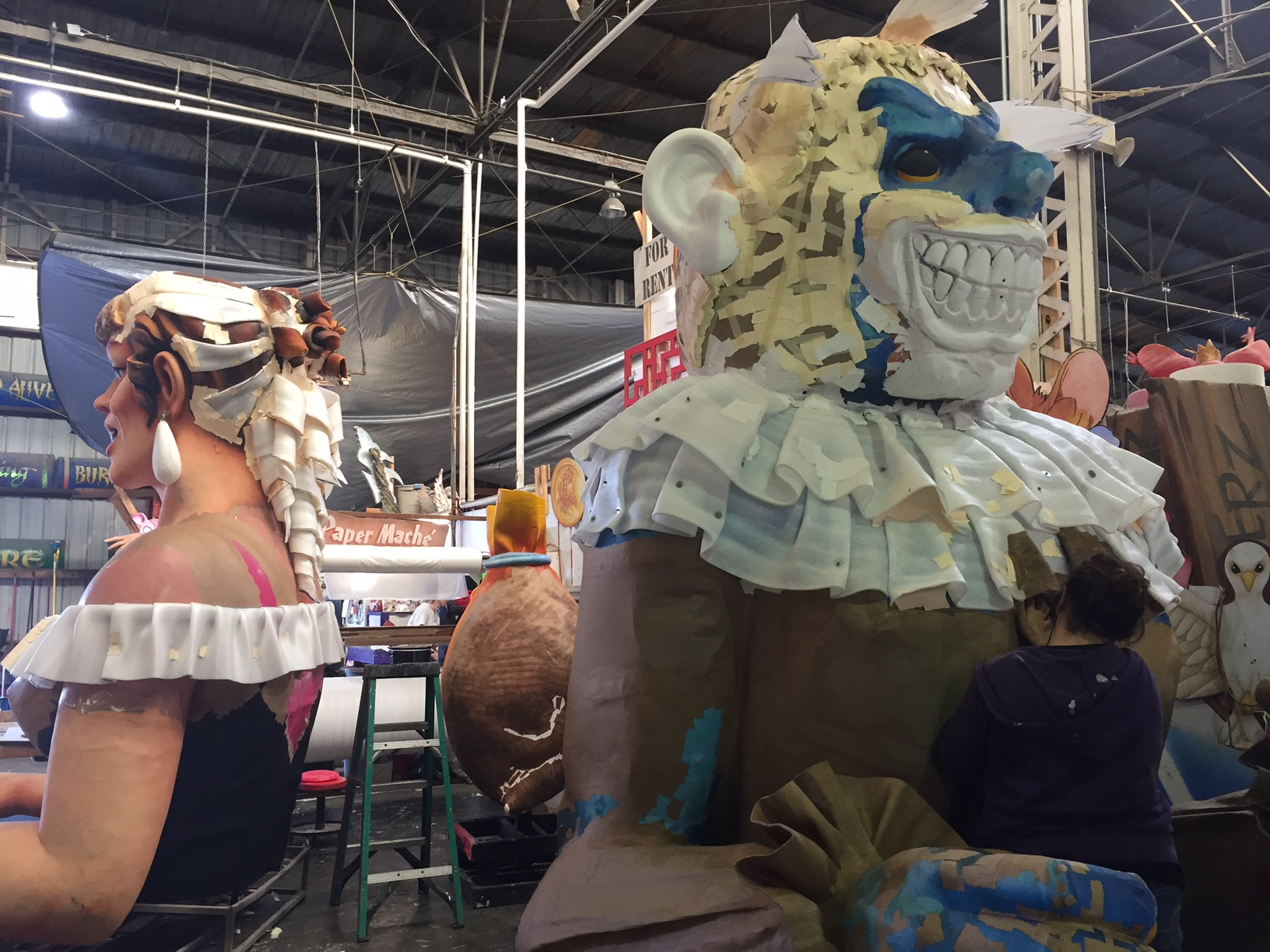 Here you can see a craftsperson changing up existing fiberglass floats by adding paper mache and paint to last year's models for a whole new look.