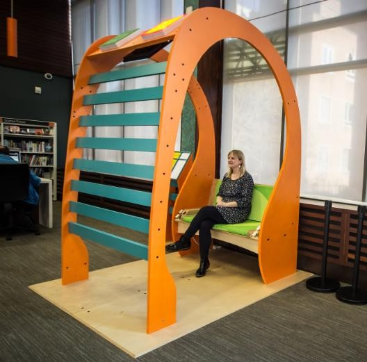 A patron at the Exeter Library enjoys The Listening Booth, which features Audio Spotlight directional sound technology