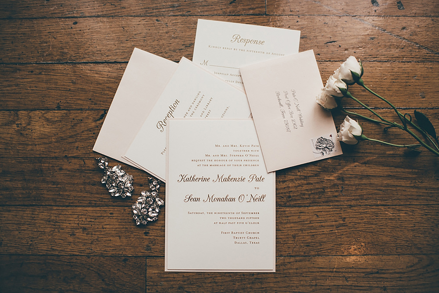 Dallas Scottish Rite Library and Museum wedding invitations with gold writing and white flowers on wood floor