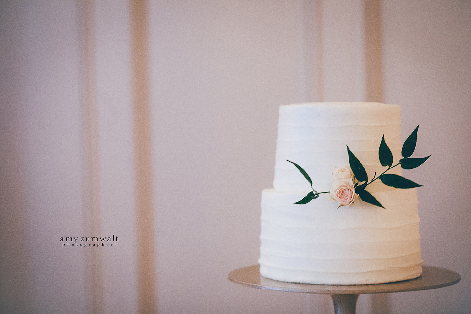 Wedding cake with one flower and greenery on gold stand