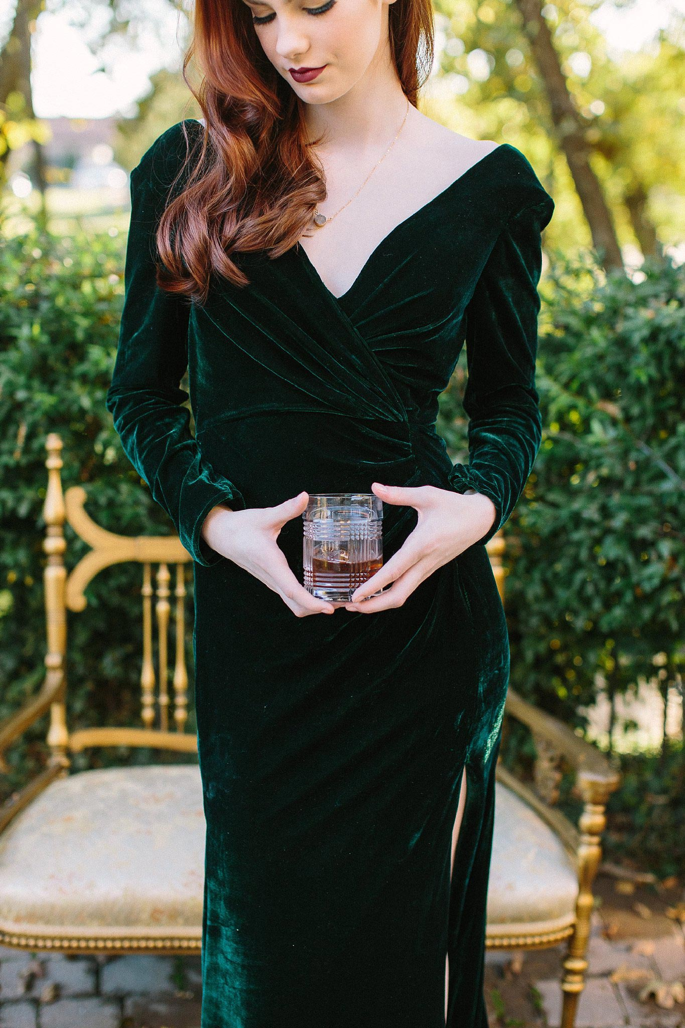 aristide mansfield wedding bridesmaid with velvet green dress holding glass of whiskey