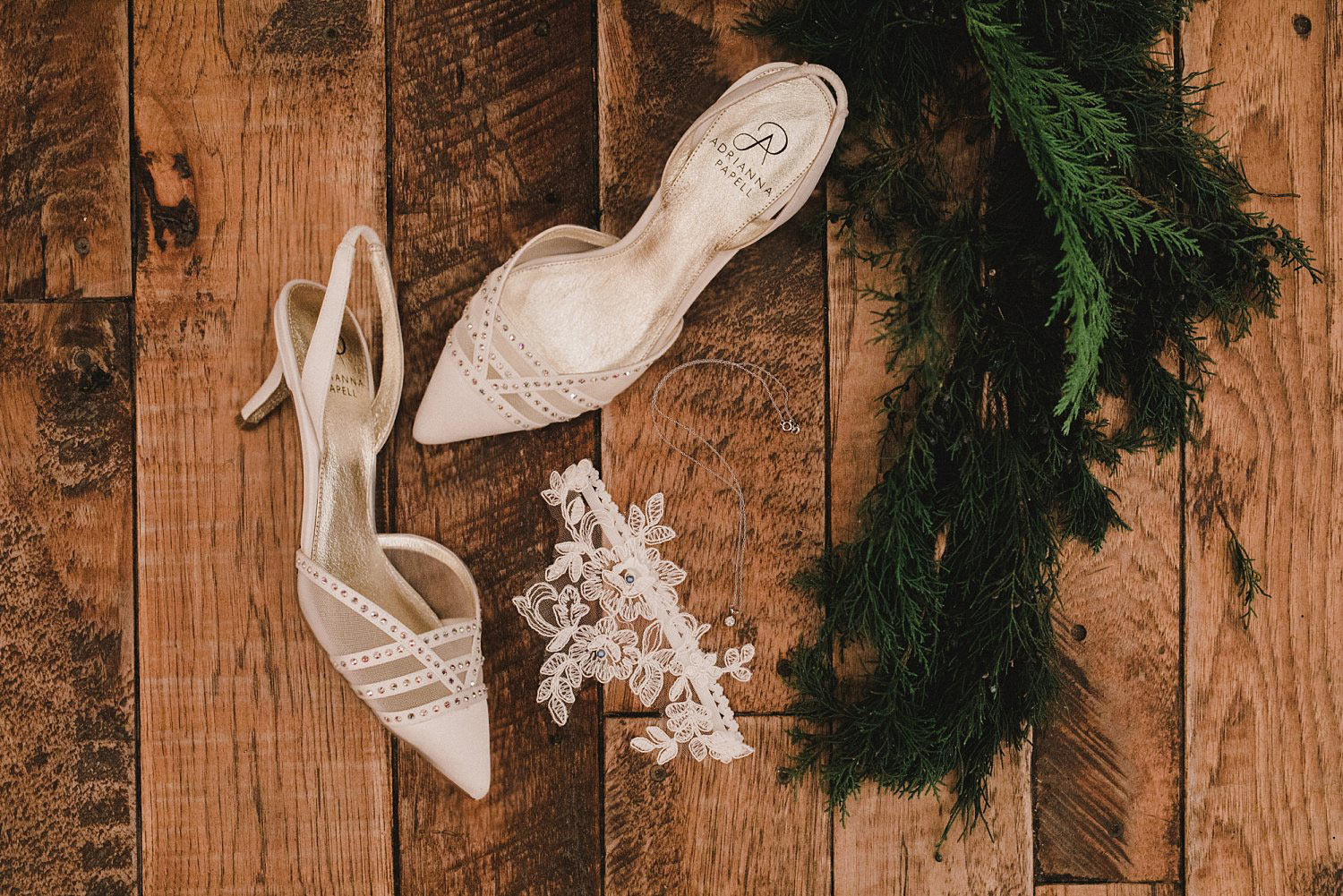 Hollow Hill Event Center Wedding bride;s shoes and garder with evergreen greenery