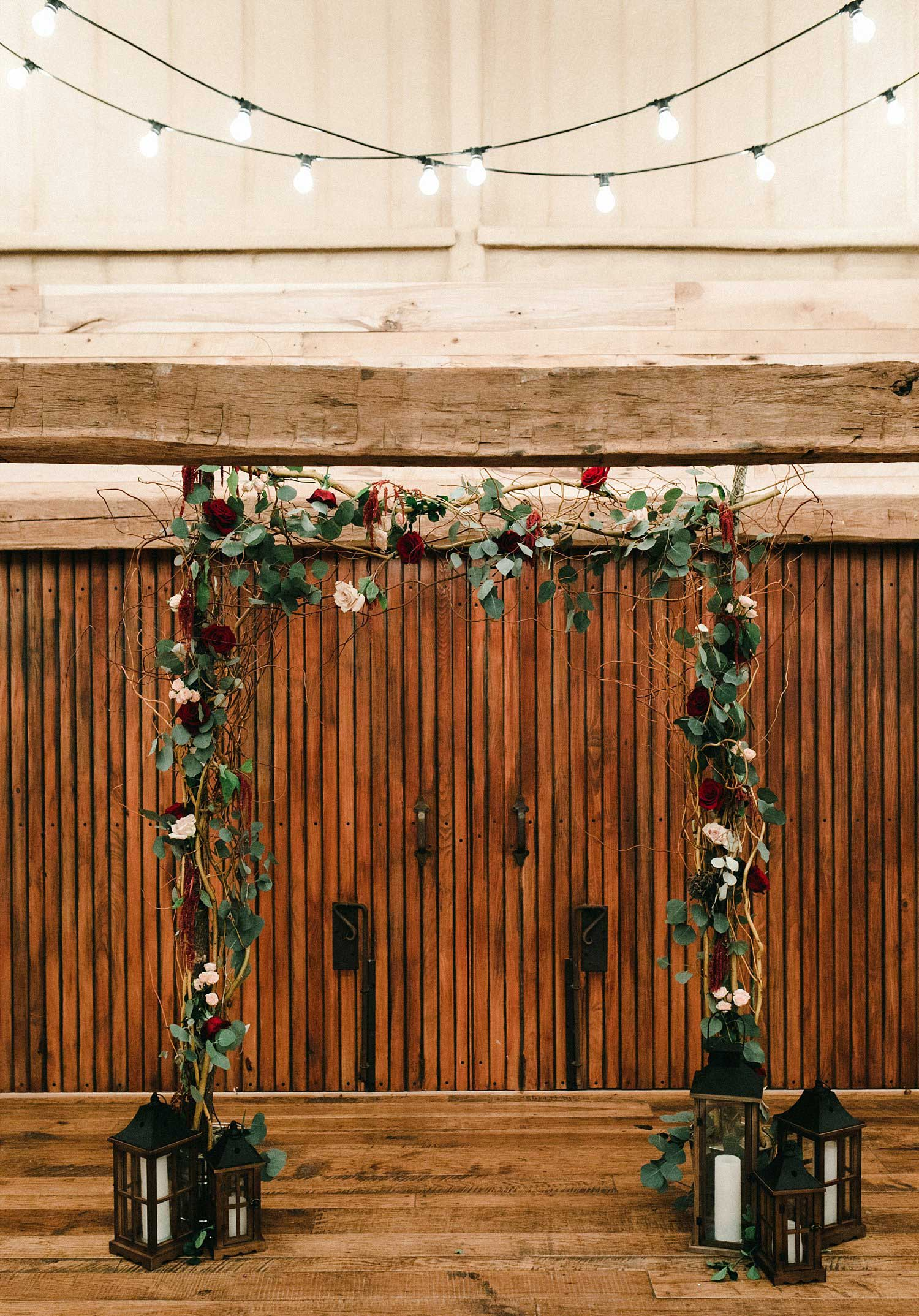 Hollow Hill Farm Event Center Wedding ceremony archway with wooden lanterns