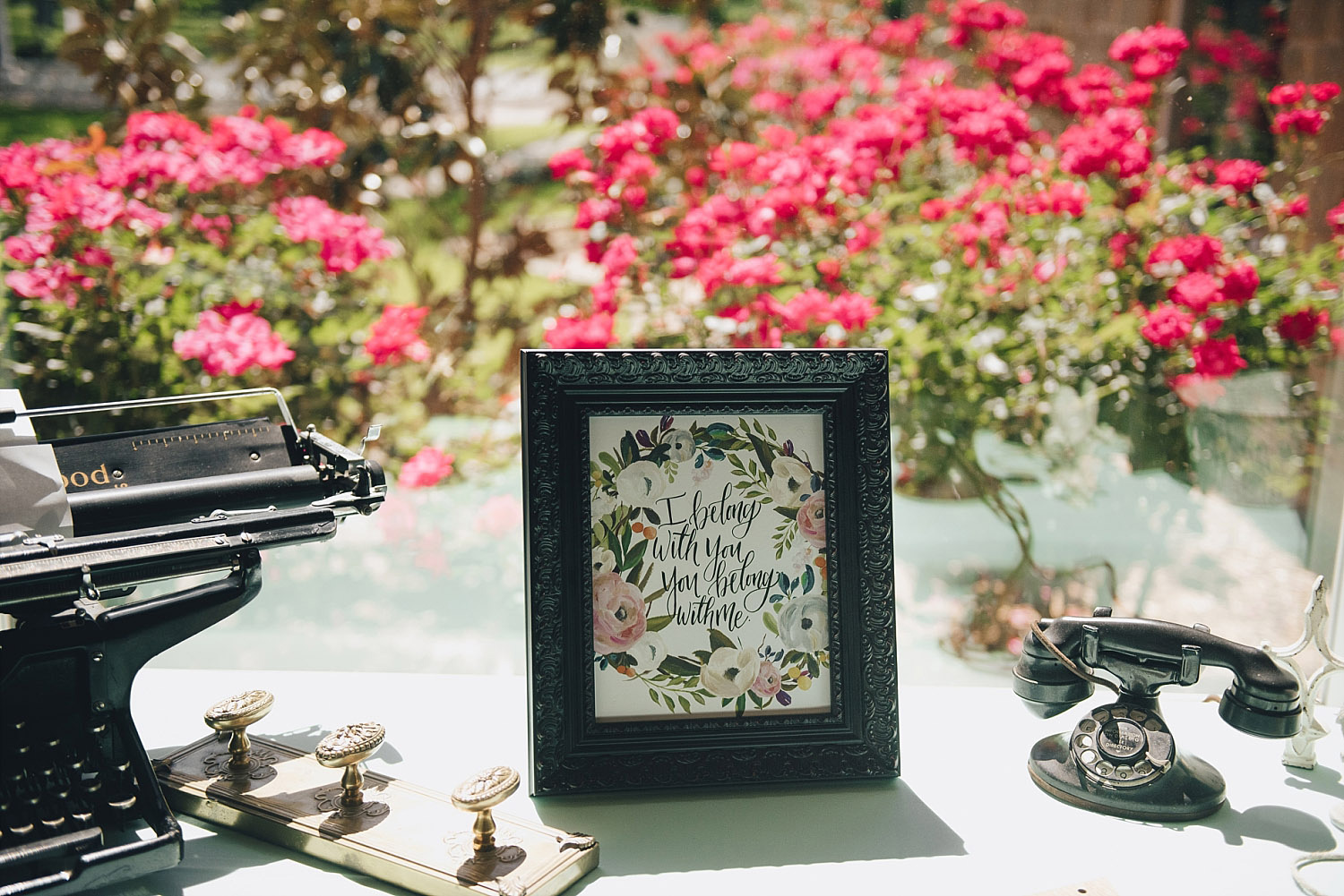 The Orchard Azle wedding floral welcome sign next to typewriter