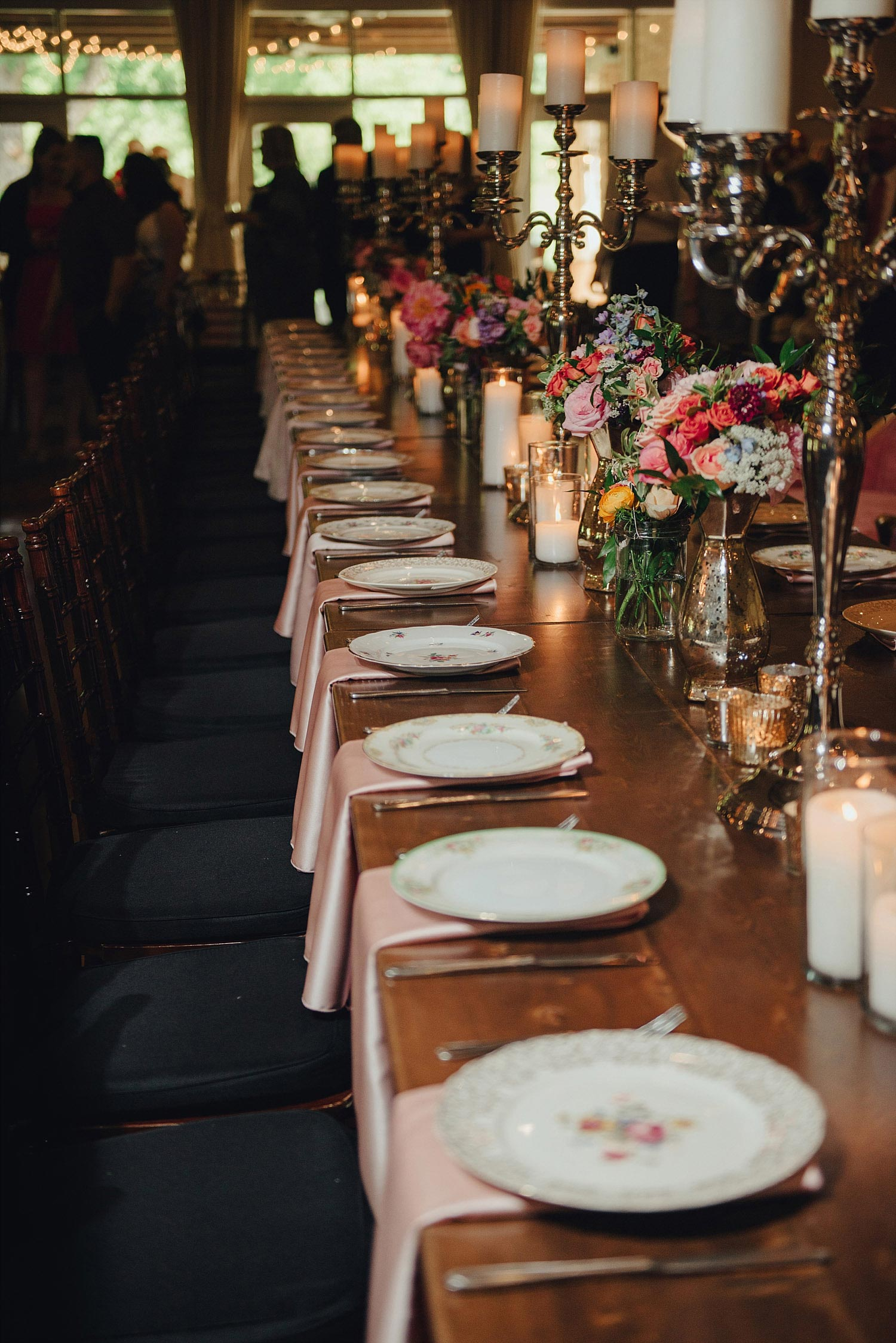 The Orchard Azle wedding wood farm table with vintage plates and candelabras