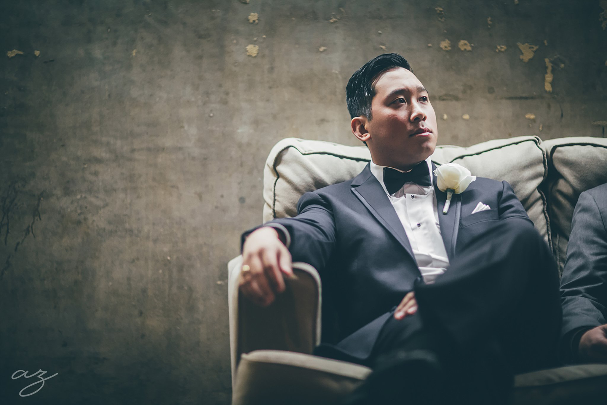 Carlisle Room wedding Groom sitting on tan chair in grey suite with a navy bowtie