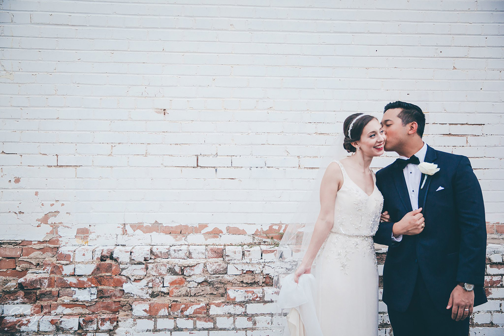 Bride and groom kissing again a whitewashed brick wall