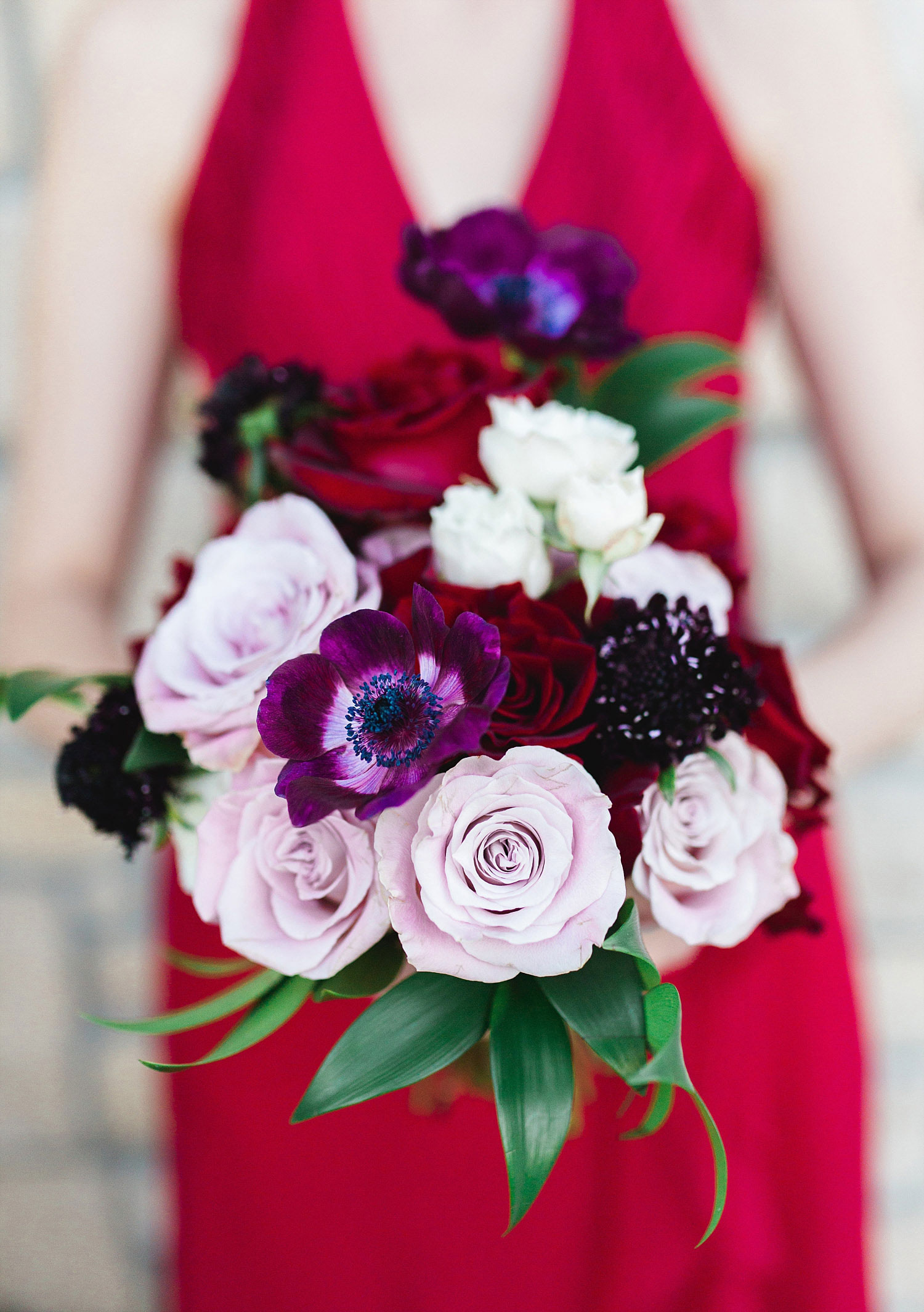 Castle at Rockwall wedding bridesmaid in red dress holding blush red and marsala bouquet