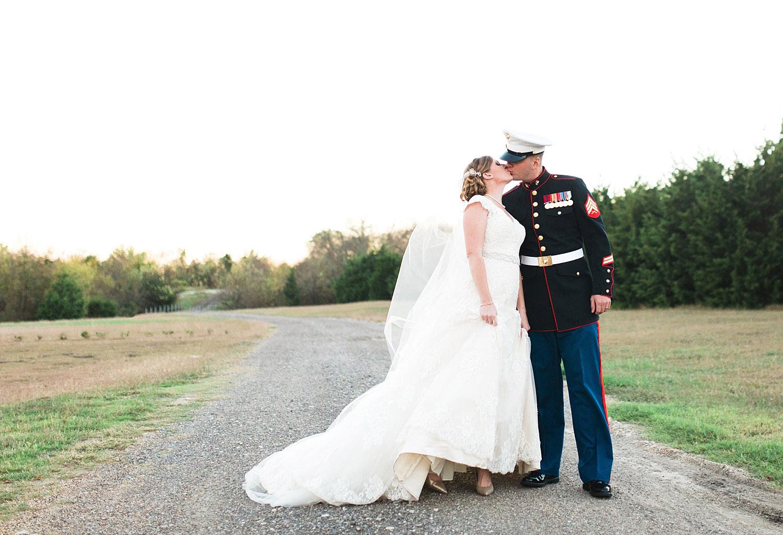 Castle at Rockwall wedding bride and marine groom kissing on gravel road