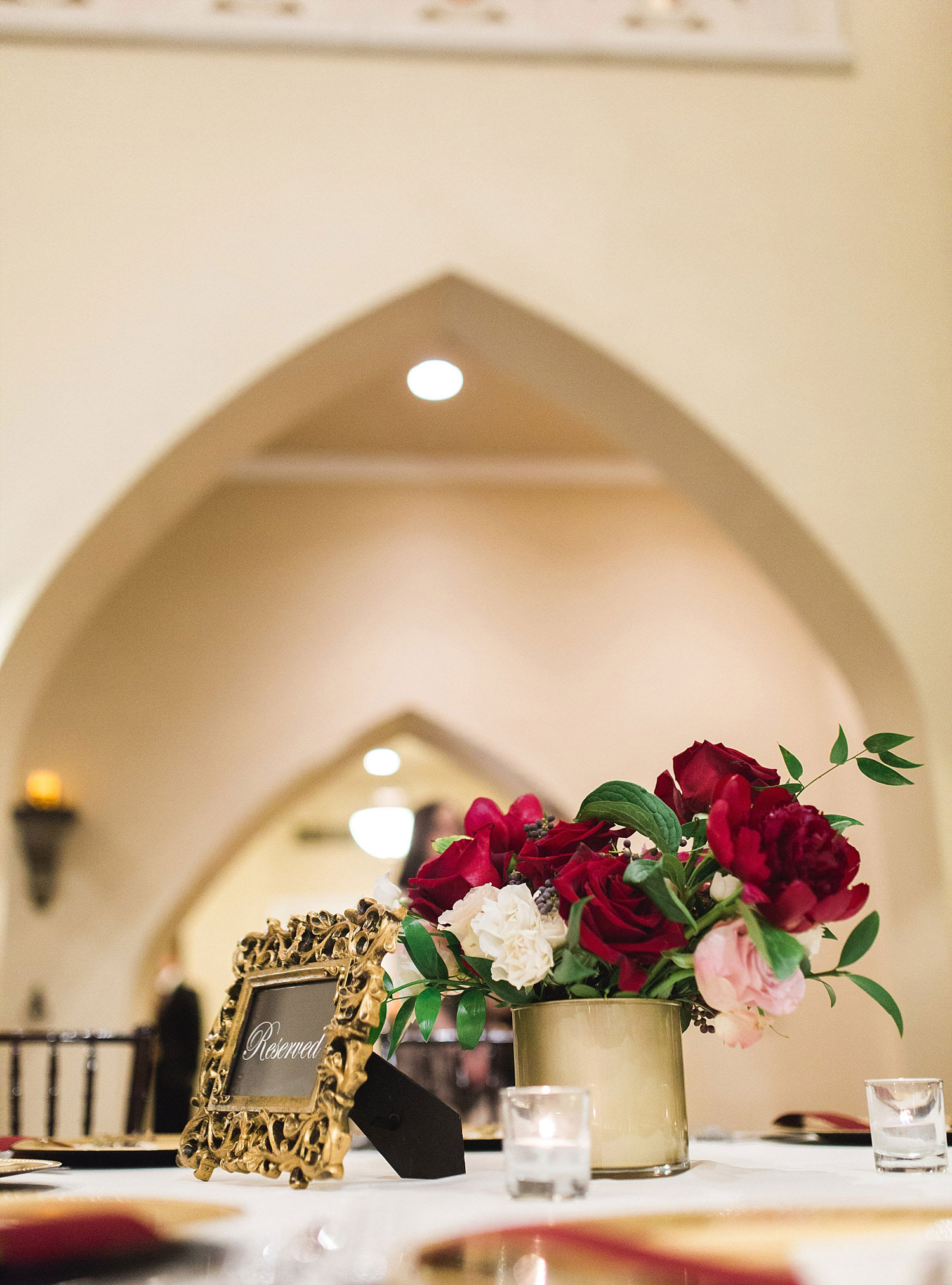 Castle at Rockwall wedding red flowers in gold vase with gold table number