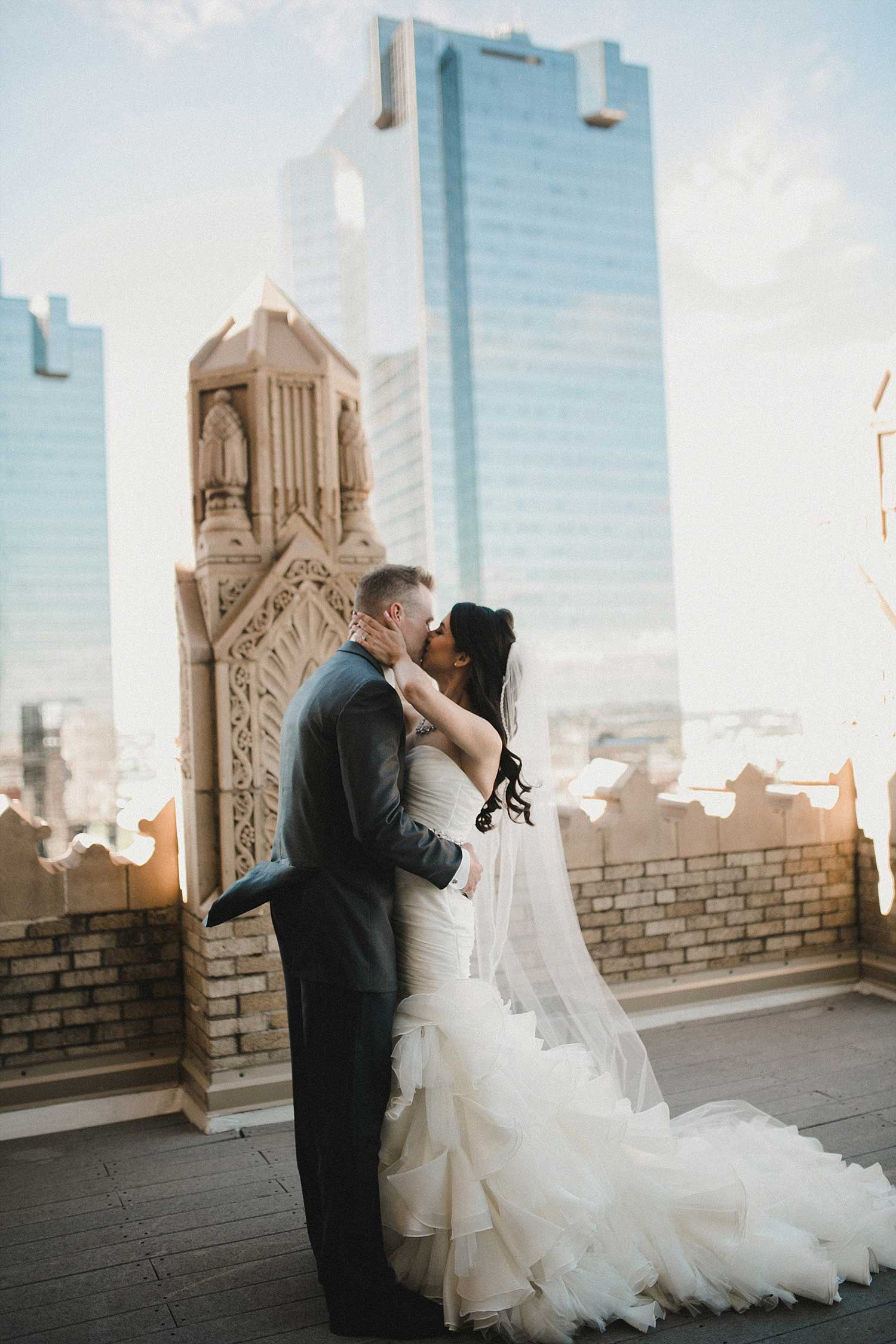 Bride and Groom kissing on the Worthington Hotel rooftop