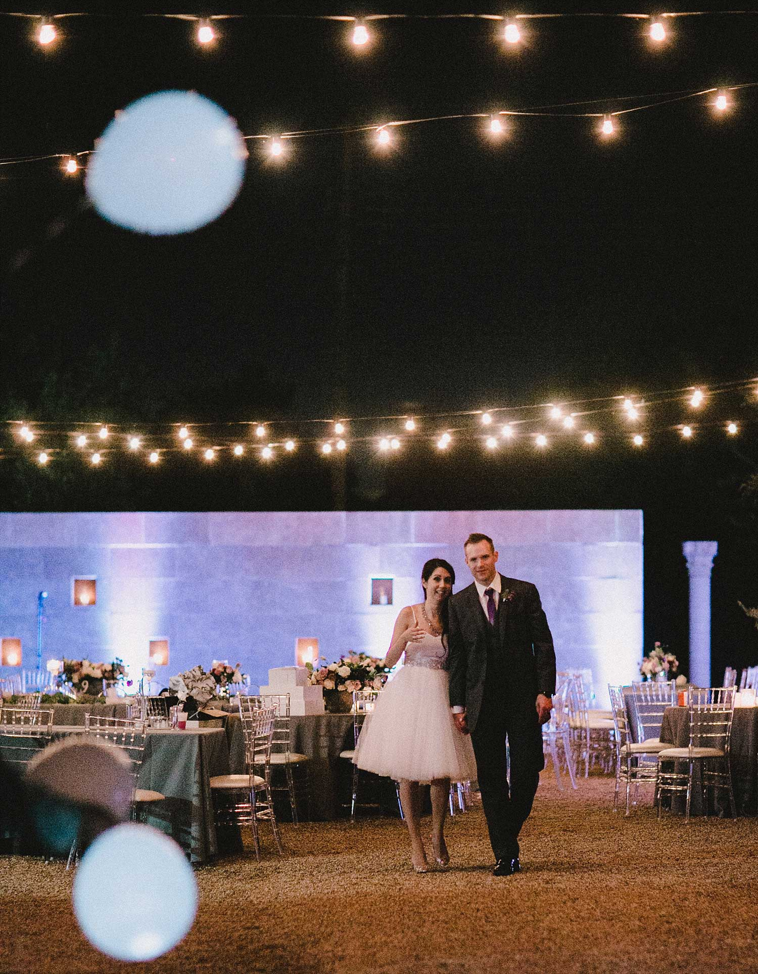 Bride in short dress next to groom with cafe lights