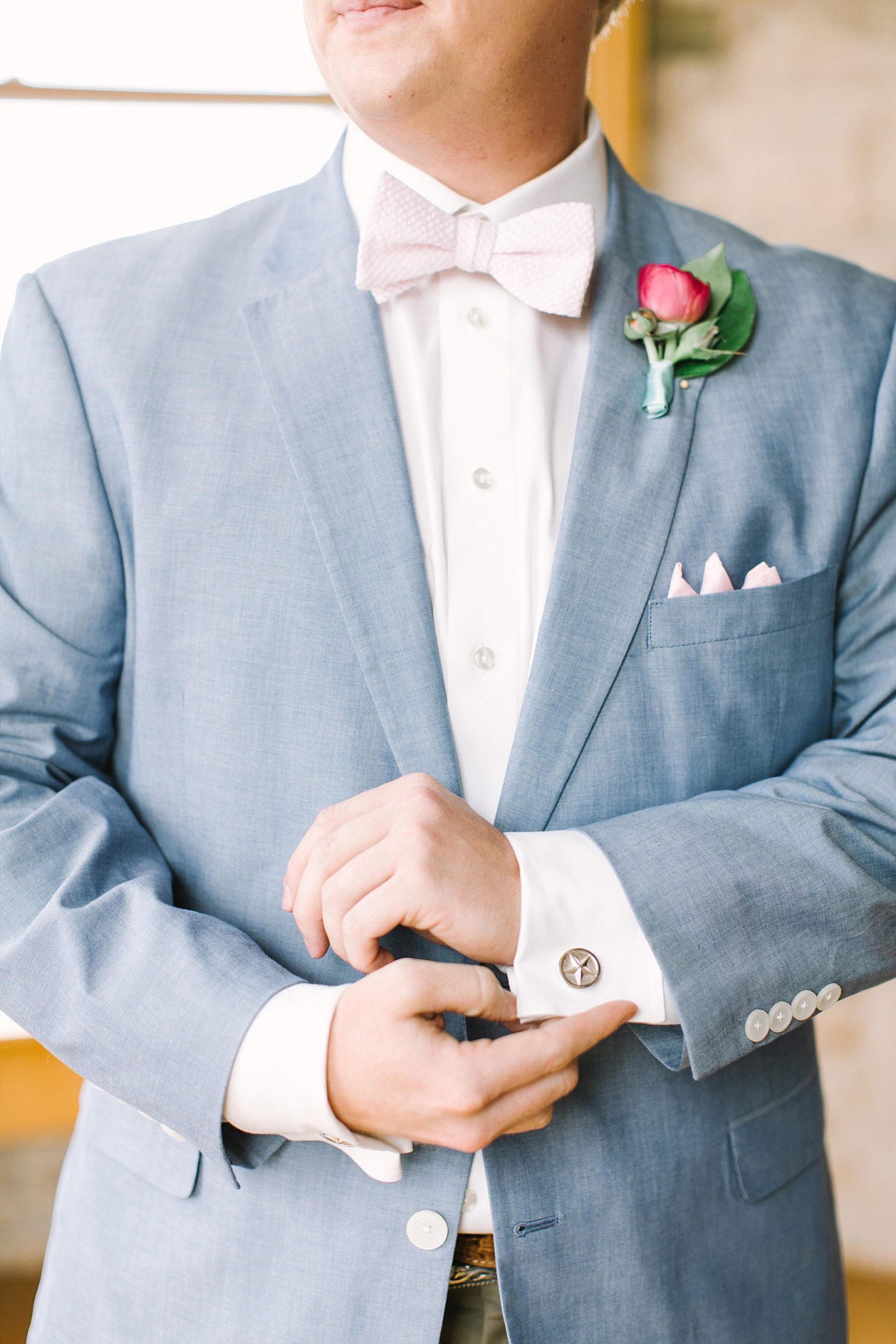 Groom where a light blue jacket, bowtie and pink boutonniere