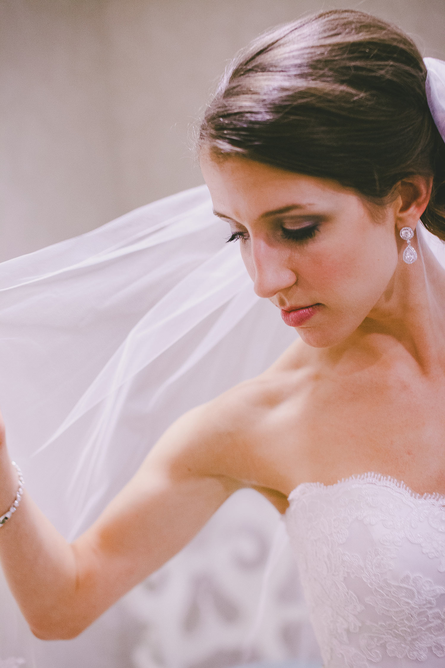 Bride with brown hair holding veil