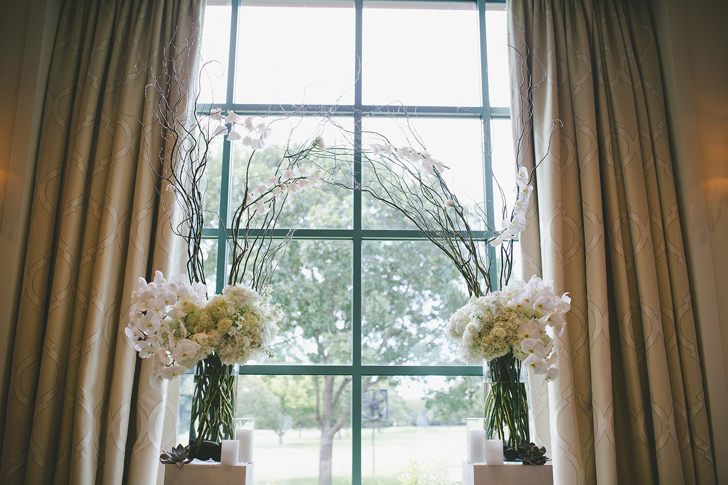 River Crest Country Clube Ceremony archway with white flowers, orchids, willow branches,  and white platforms