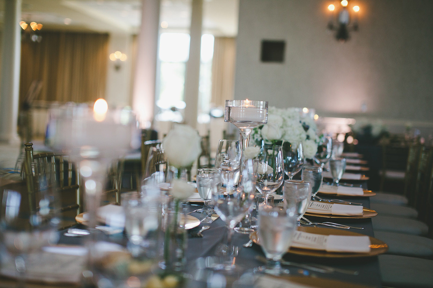 River Crest Country club grey linen with floating candles and gold chargers on table