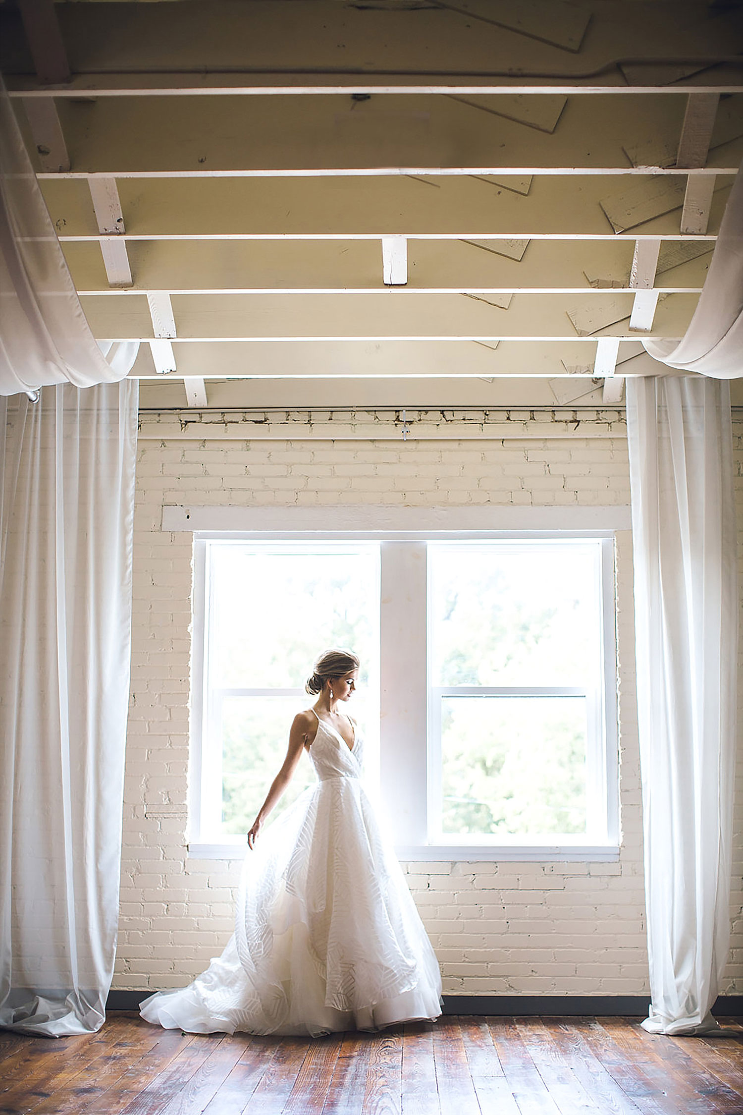 Brik Special Events Venue upstairs southern bride at window with white drapery