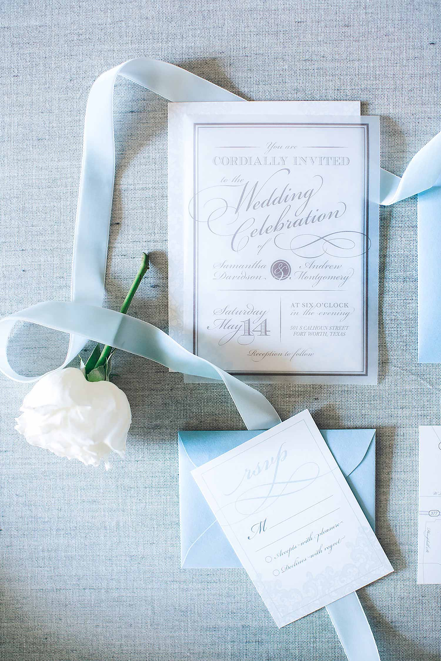 Acrylic wedding inviation and dusty blue envelope with a white rose