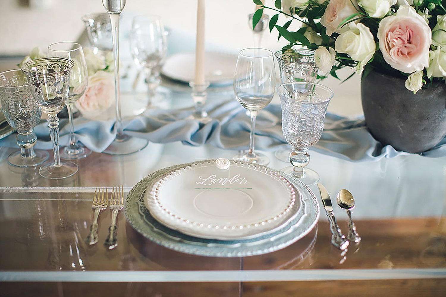 Dusty blue place setting with a acrylic place card with a white wax seal