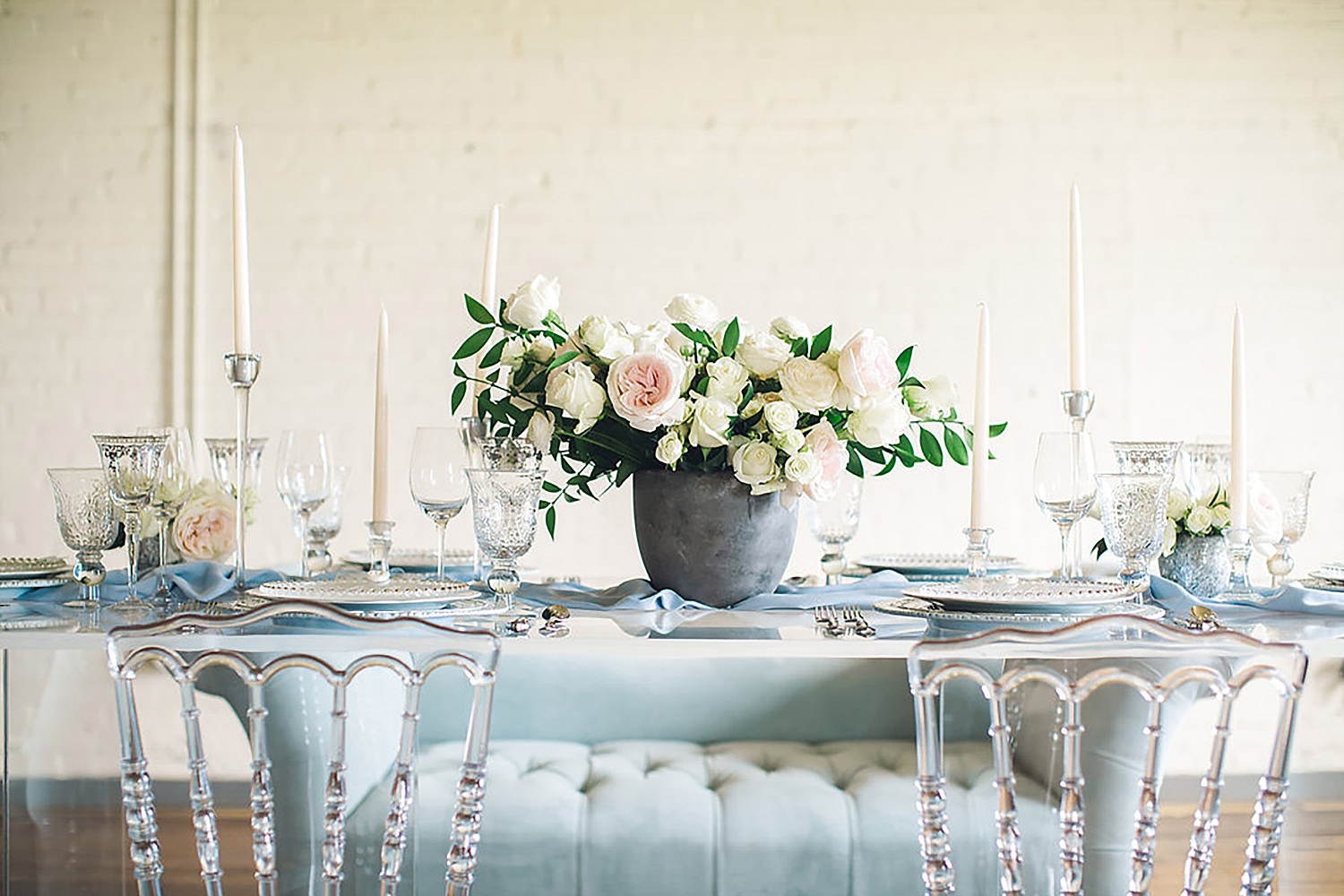 White flowers in a concrete vase on a acrylic table with ghost chairs