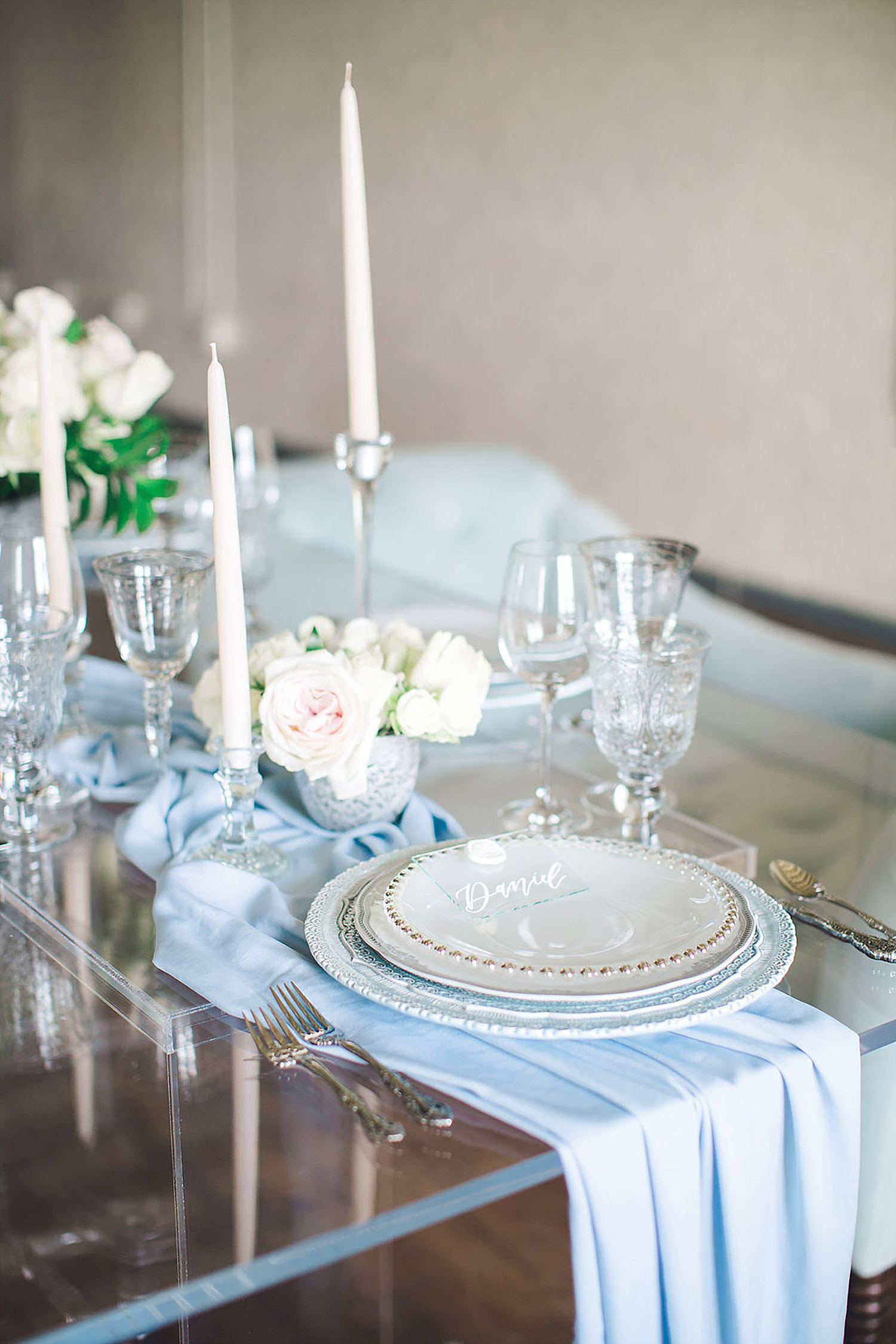A acrylic table with a dusty blue china charger and tapered candles at Brik Venue