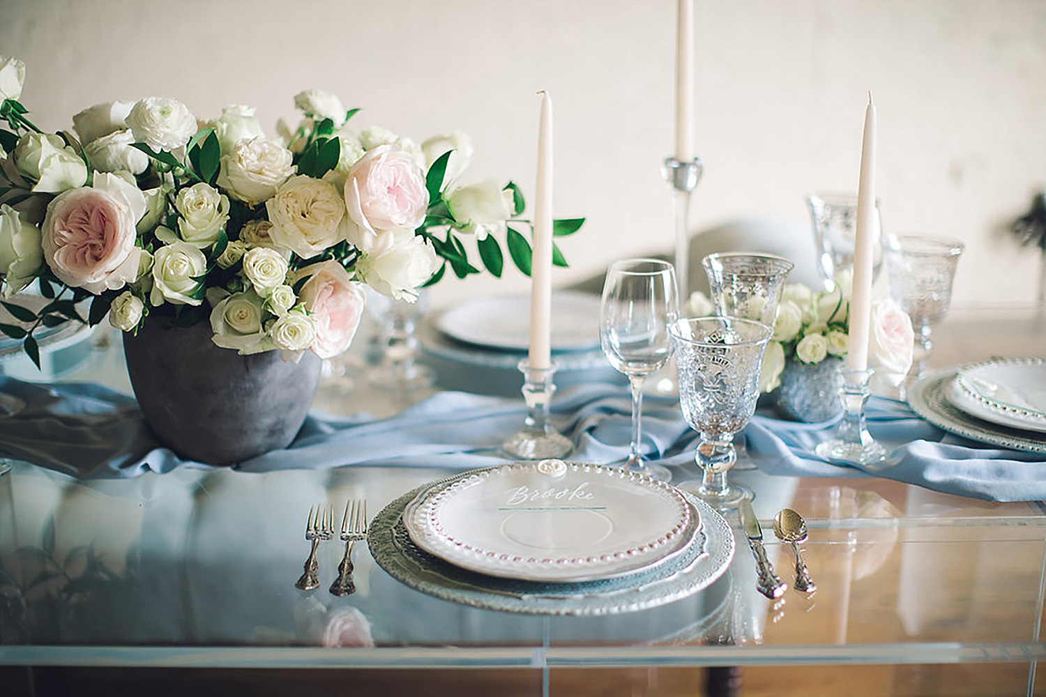 Dusty blue and white place setting with white tapered candles and white and blush flowers