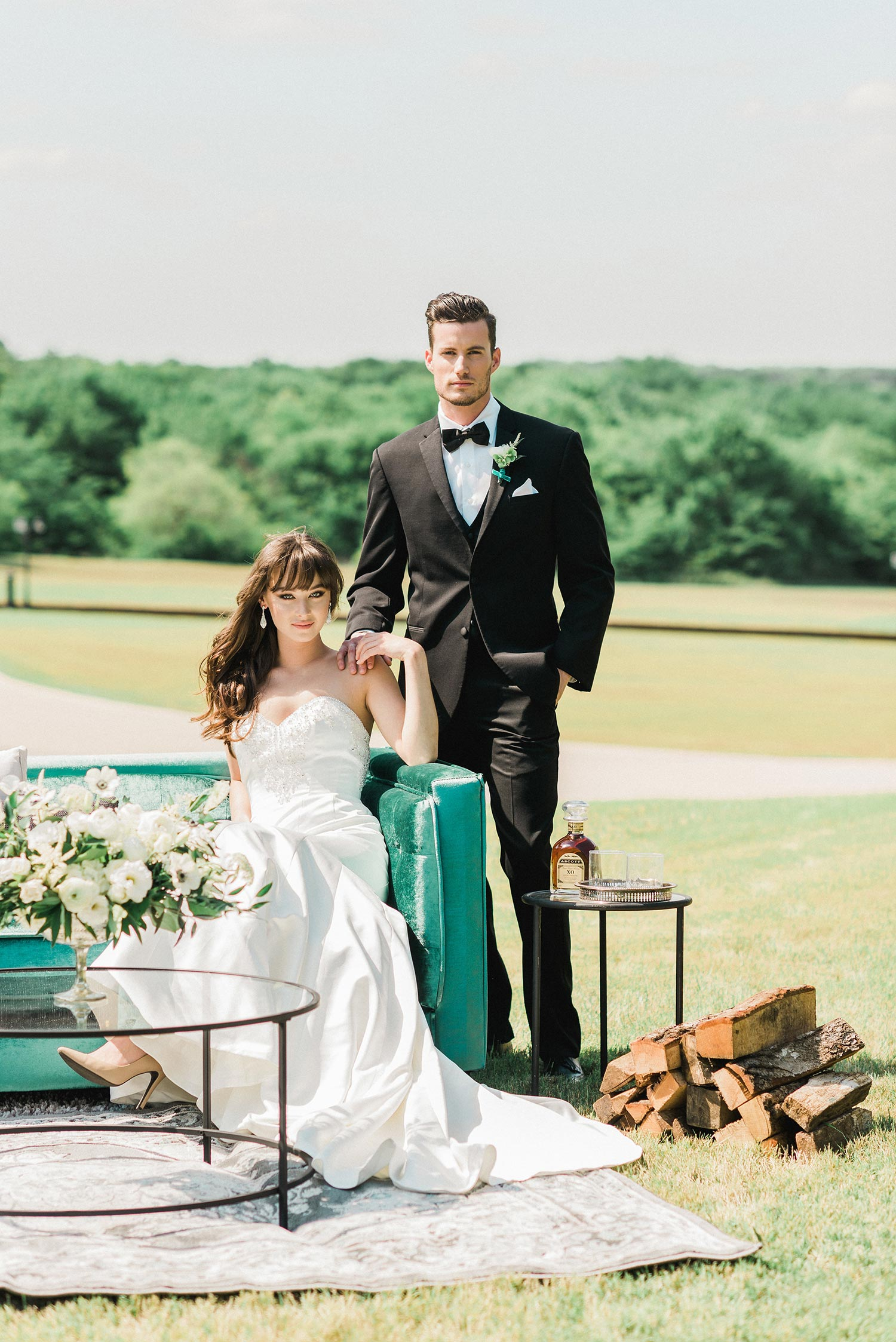 Bride and groom sitting on a emerald green sofa with firewood