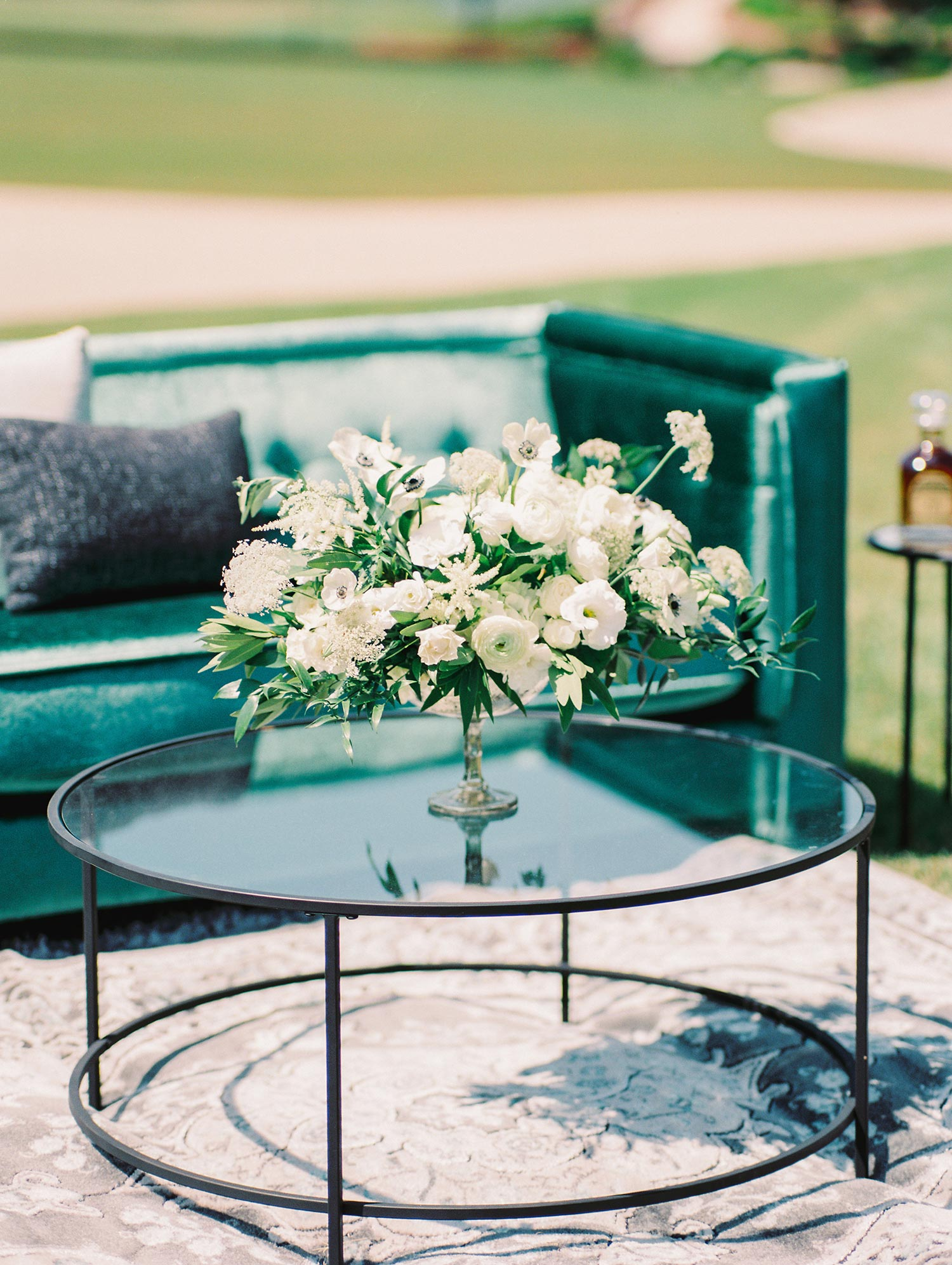 White flowers on a round coffee table at a outdoor wedding lounge