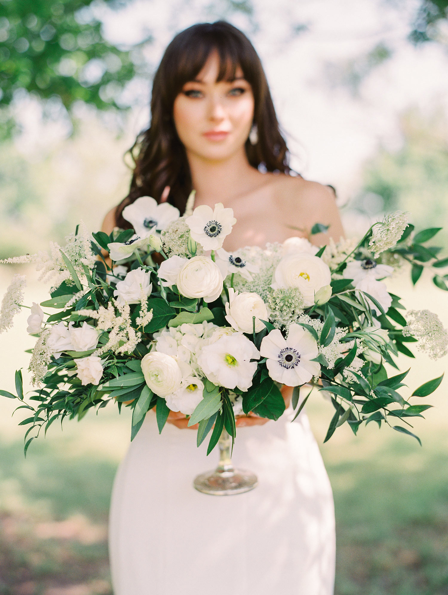 Bride holding white and green flowers in a silver vase