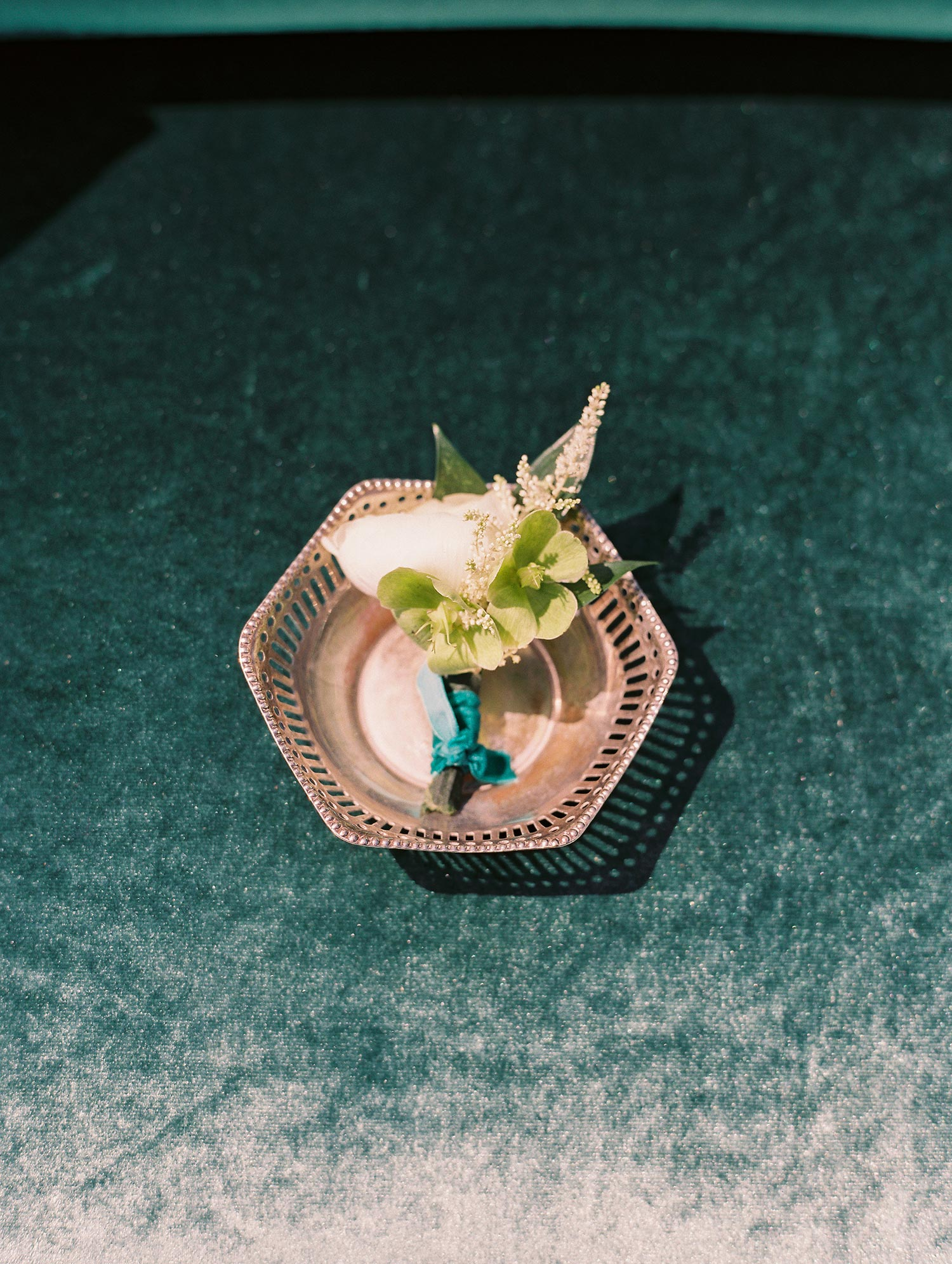 Groom's white boutonniere with a velvet green tie