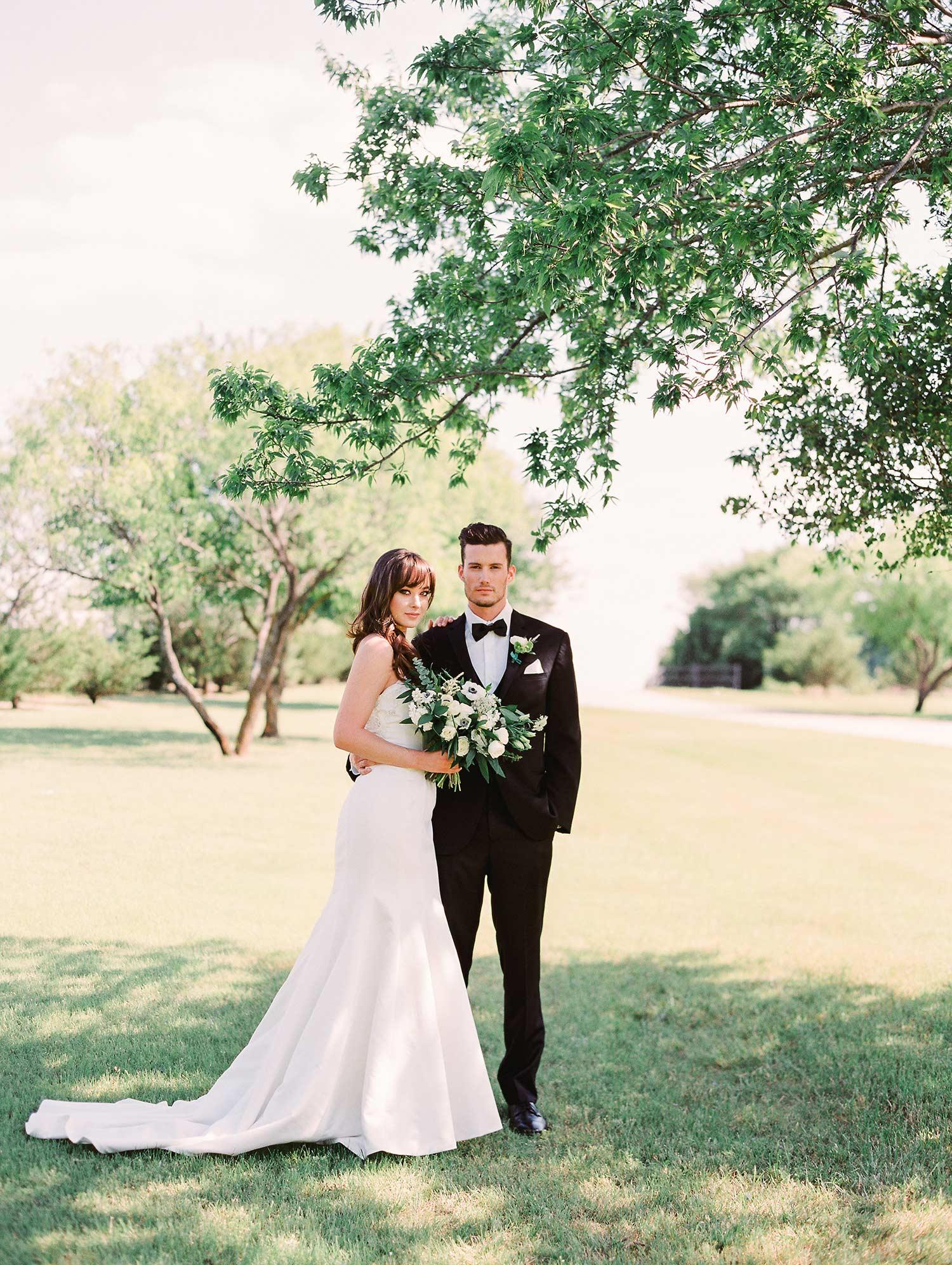Bride in long satin dress standing outside with groom in black tuxedo