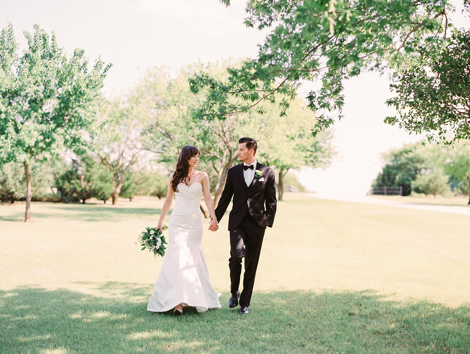 Bridea and groom walking outside and big open field in classic wedding attire at Miletone in Denton