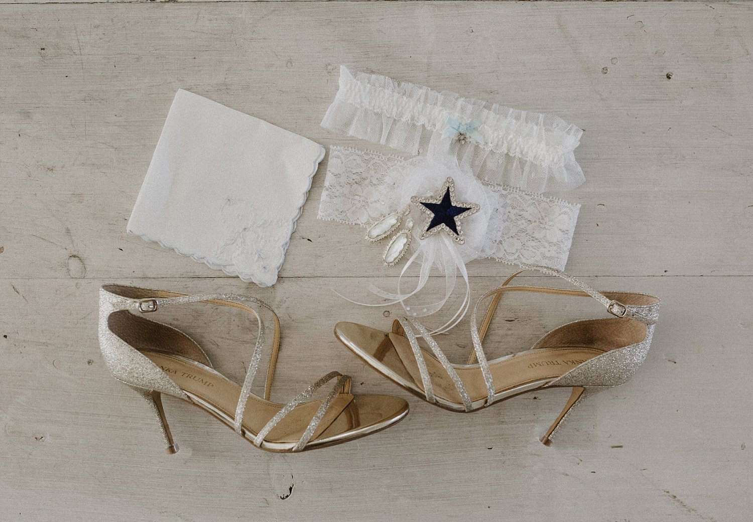 Nude wedding shoes with a dallas cowboy cheerleader garter on white wood floor
