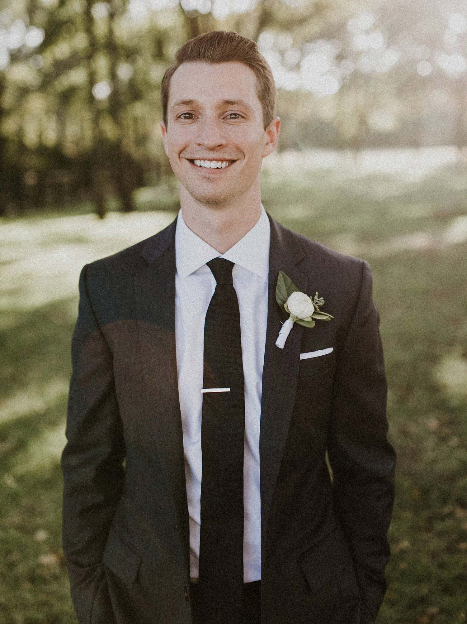 We love this classic groom's attire for this barn wedding.  He wore a dark grey suite, black tie, and white boutonniere