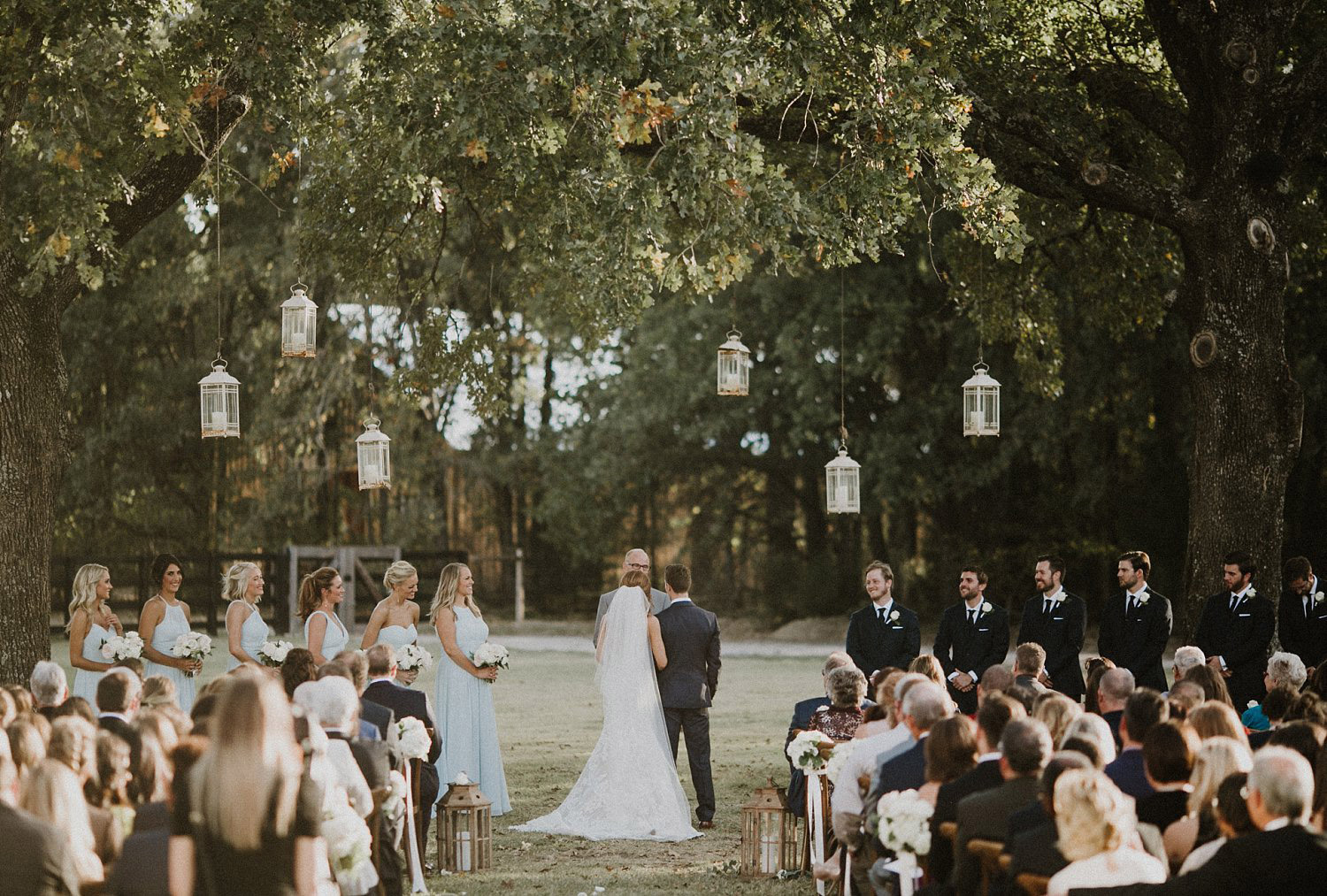 White Sparrow Barn outdoor ceremony with hanging white lanterns with dusty blue bridesmaid dresses