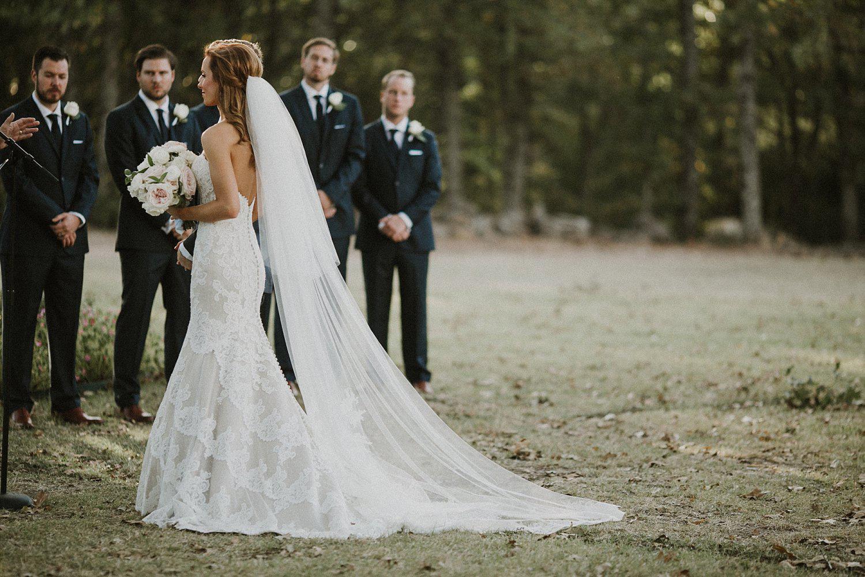 Dallas Cowboy Cheerleader bride at White Sparrow Barn outdoor ceremony with long cathedral veil