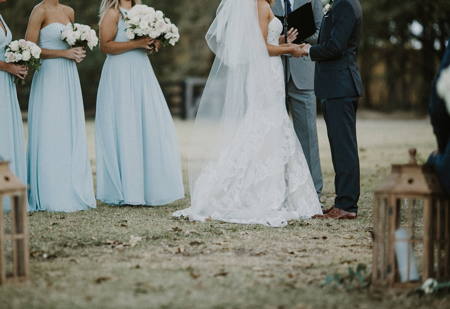 Bridesmaids in long bridesmaid dresses holding white flowers at outdoor ceremony