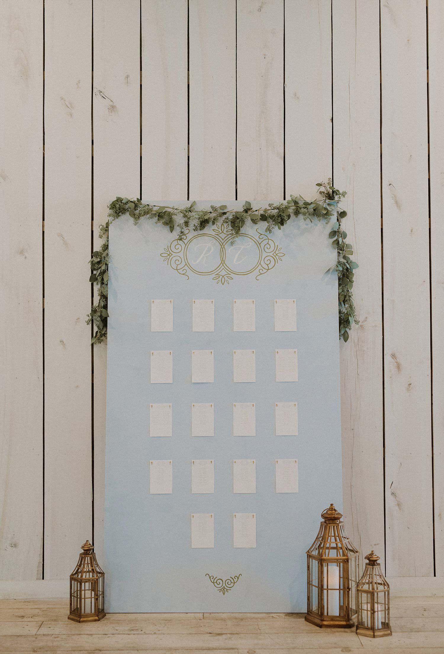 DIY dusty blue seating chart with gold lanterns and gold monogram at White Sparrow Barn