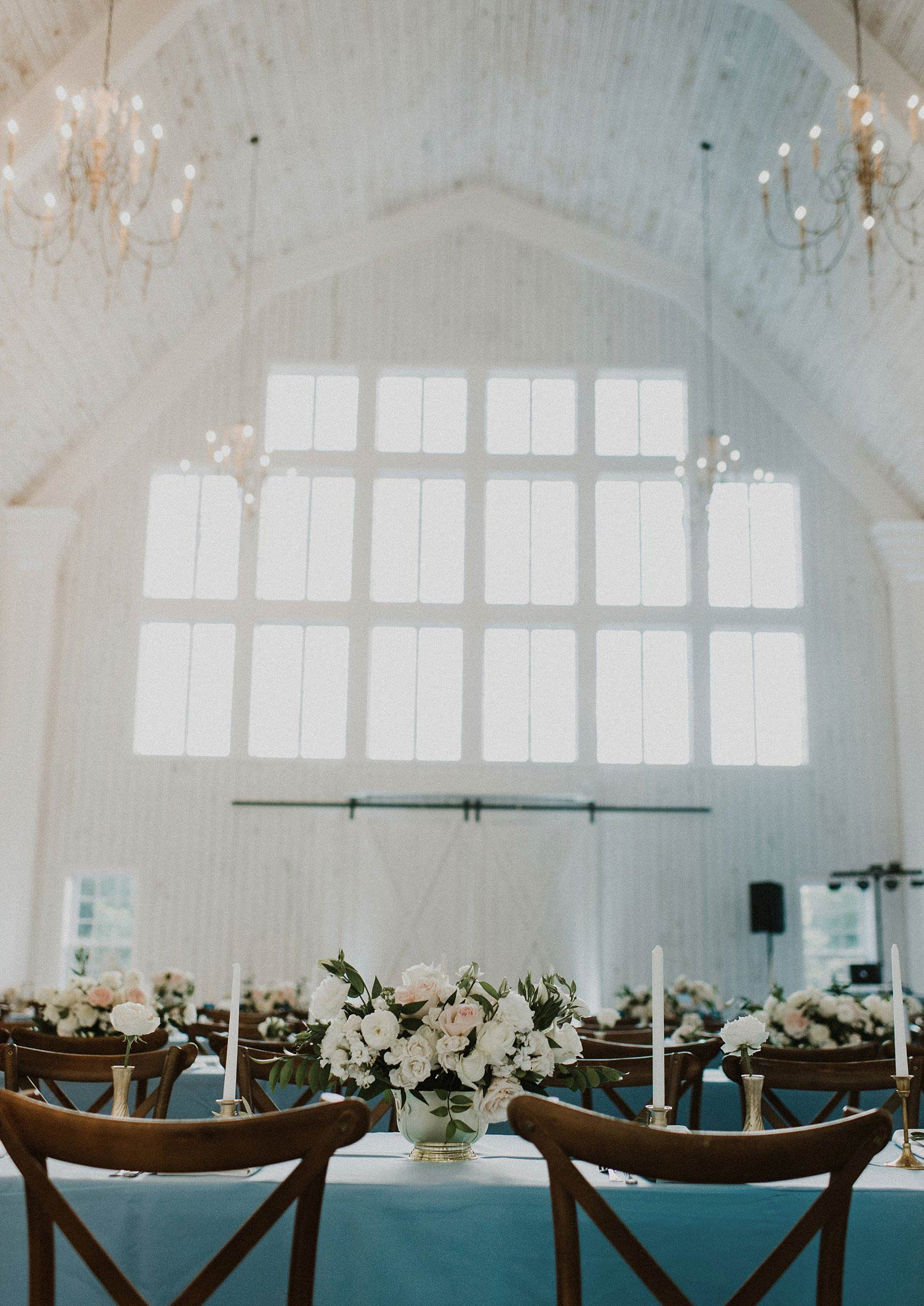 White Sparrow Barn wedding reception dusty blue linens and white and blush flowers in gold vase