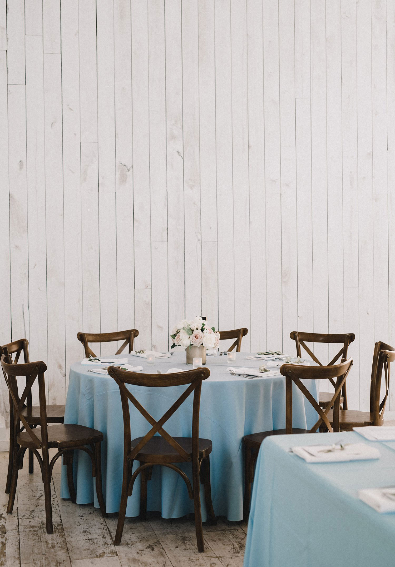 White Sparrow Barn wedding dusty blue linen on round table with cross back chairs