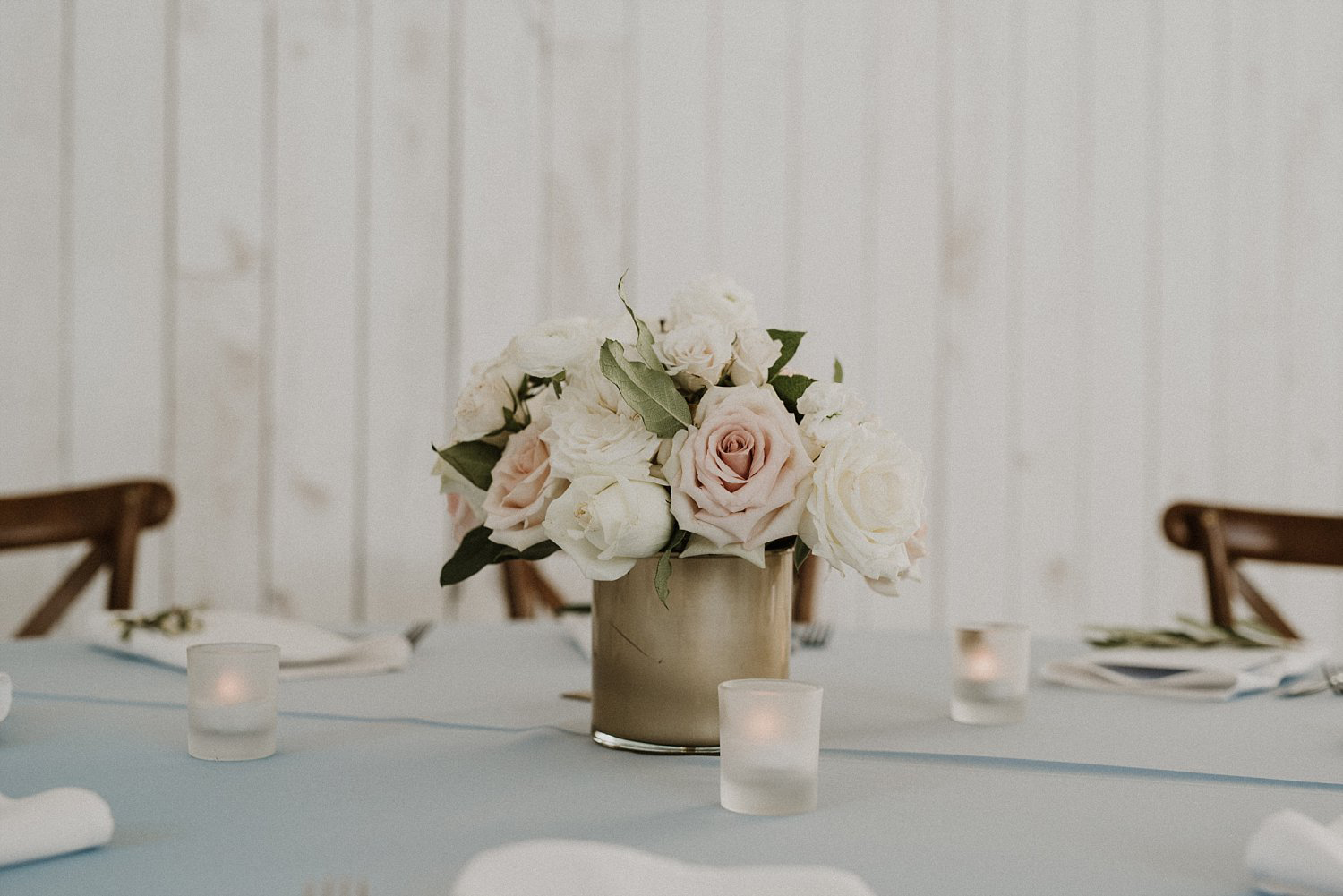 Simple white and blush flower arrangement in a gold vase on a light blue linen