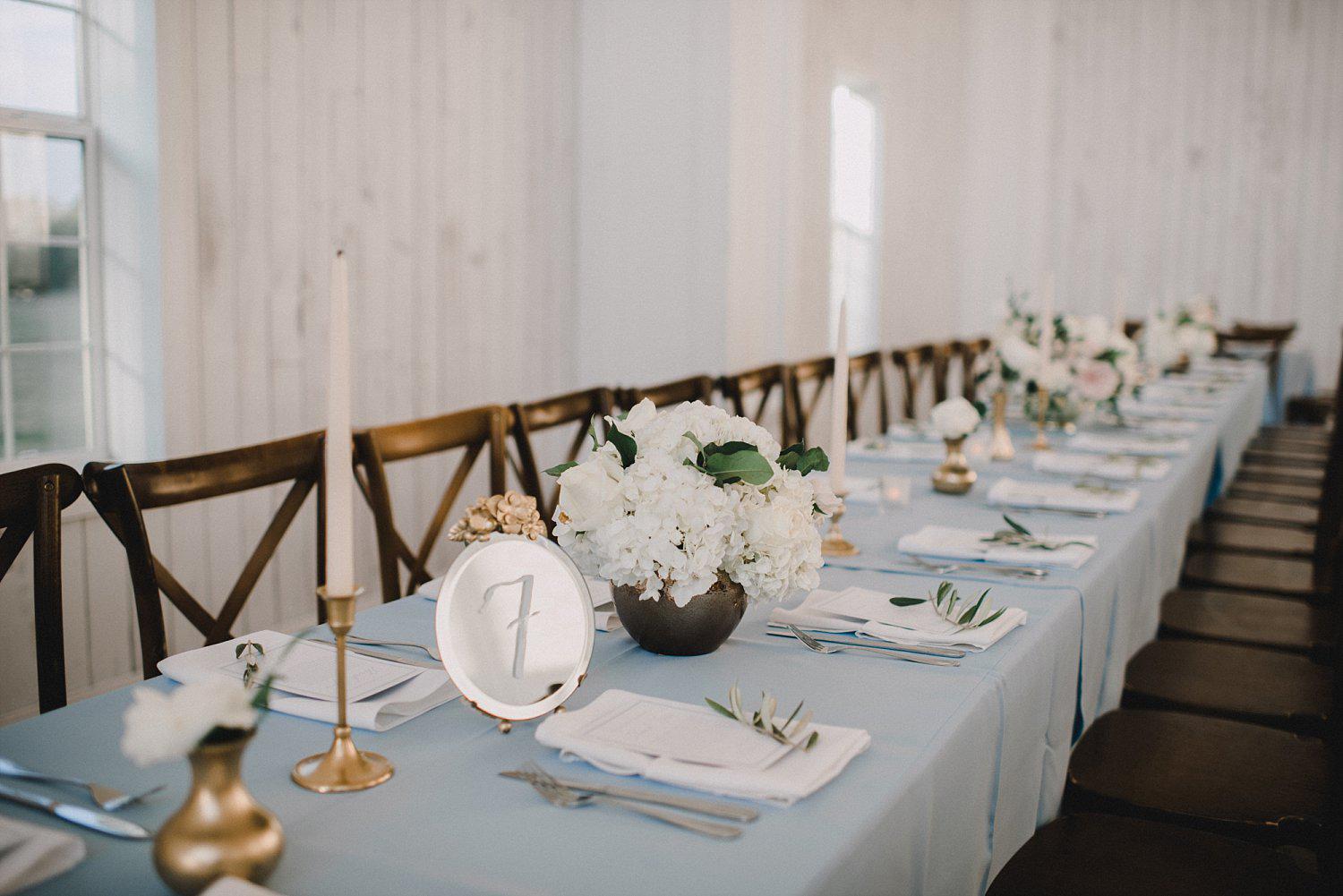 Light blue table with vitnage mirror table numbers and tapered candles