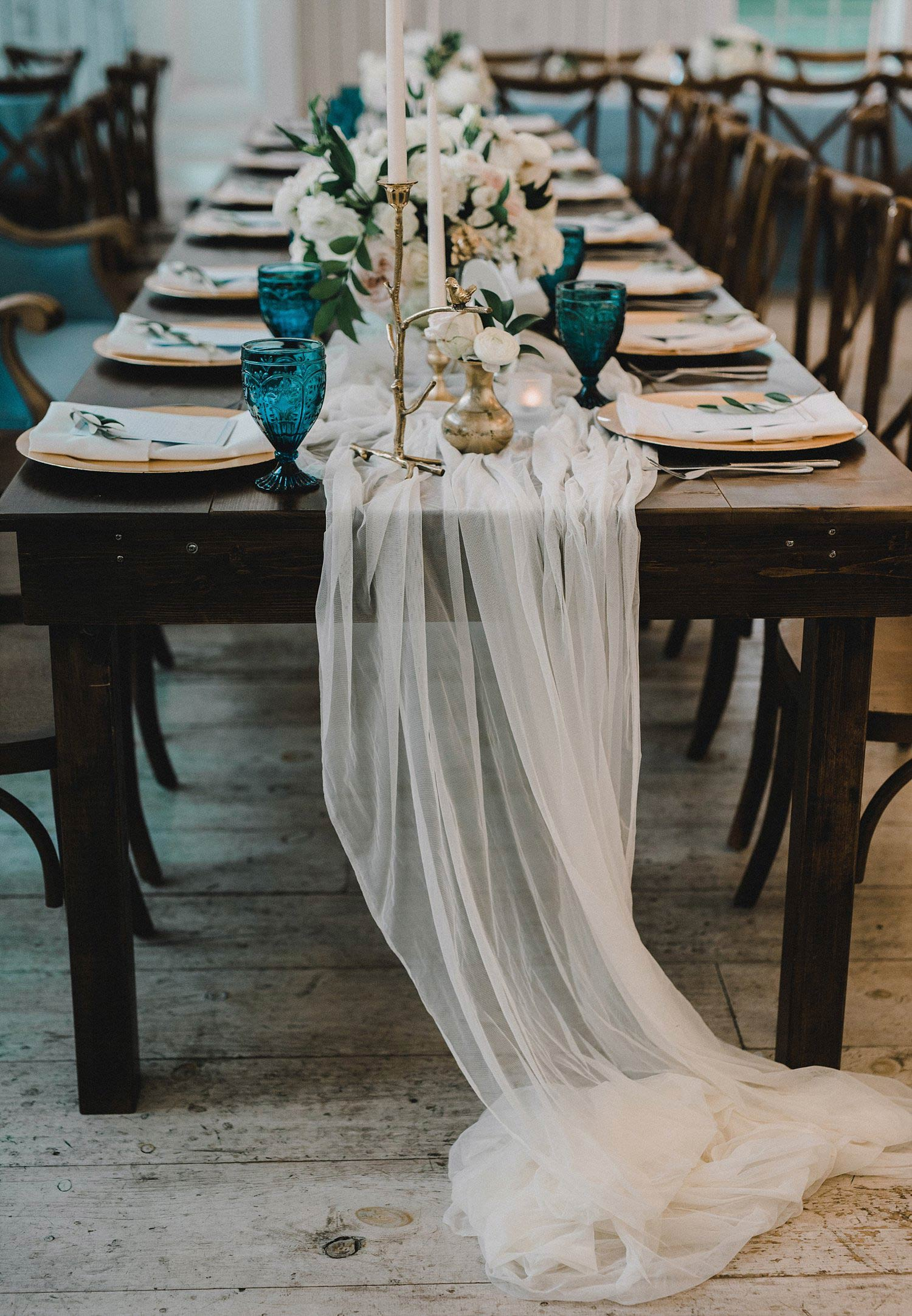 Long white runner on farm table head table with blue vintage goblets