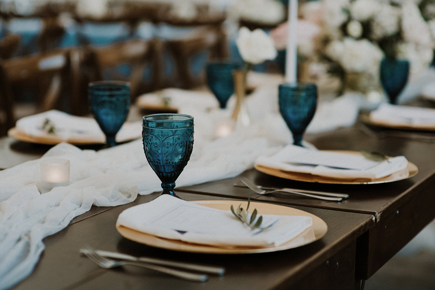 Gold charger with white napkin and dark blue vintage goblet