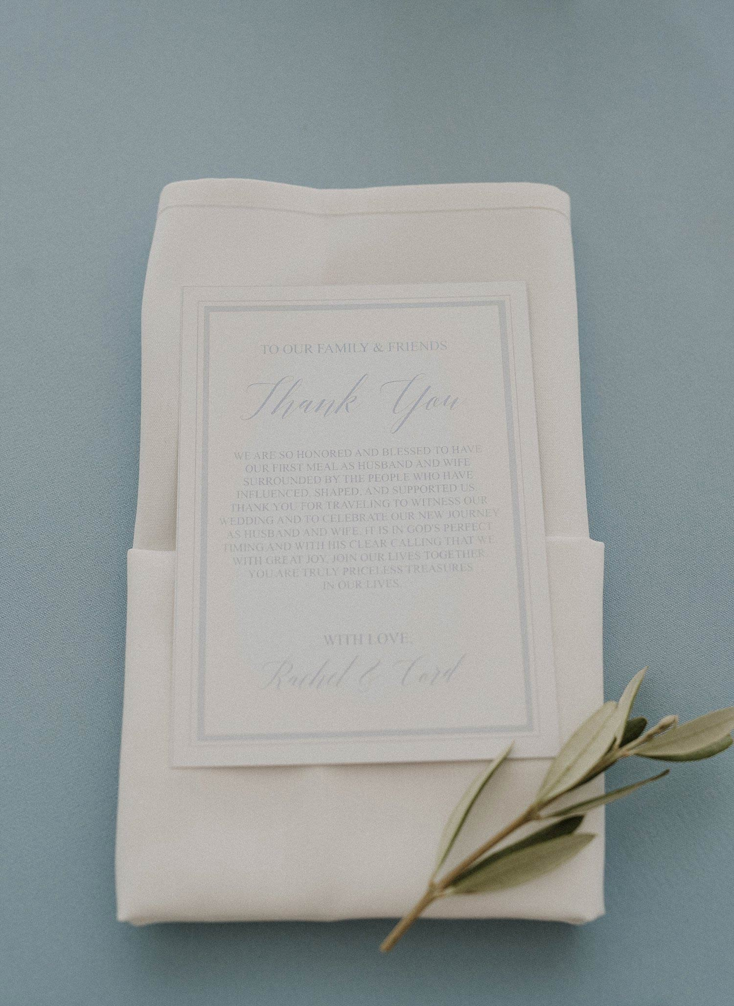 Menu on folded napking with olive branch on top of light blue linen