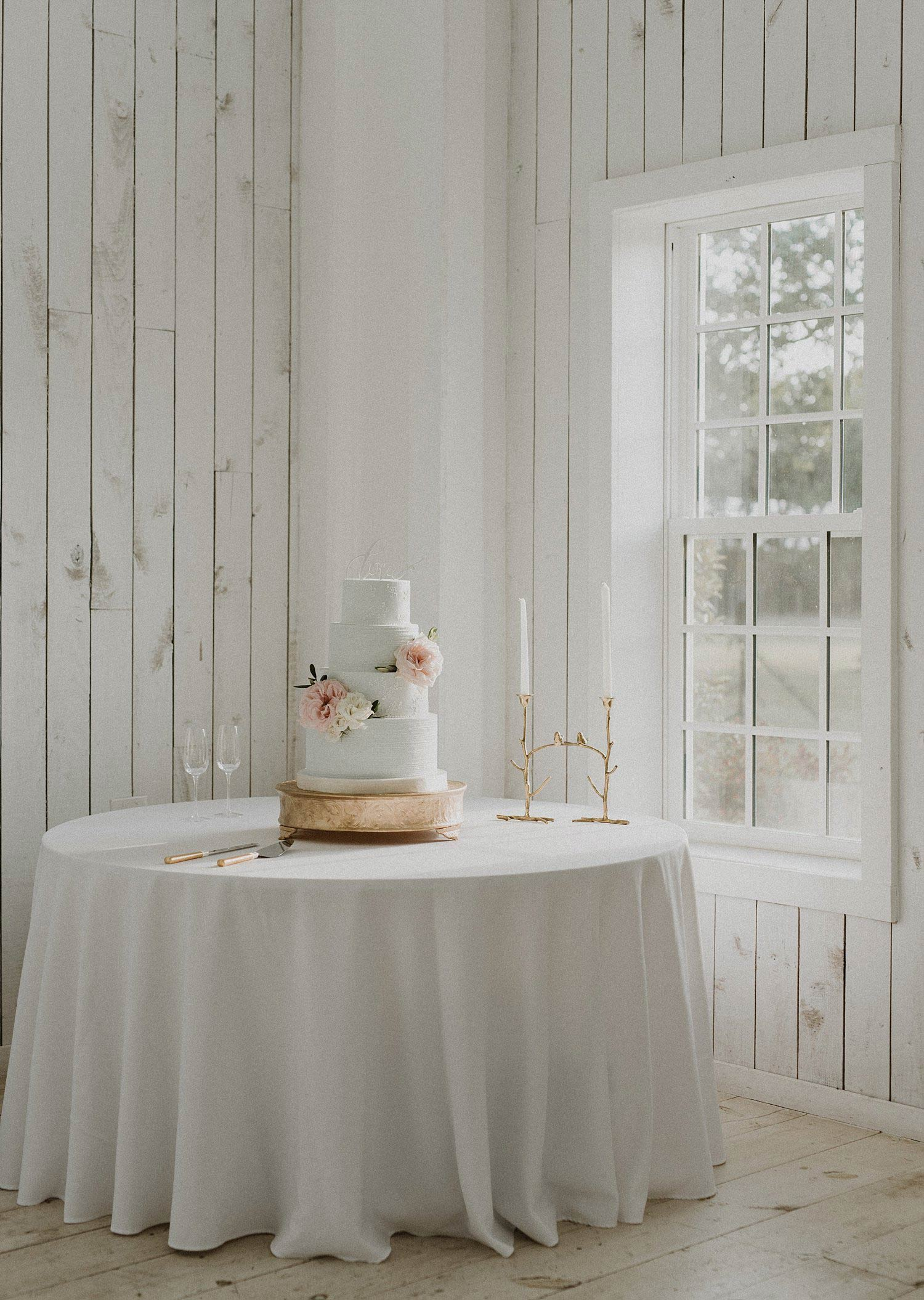 White Sparrow Barn dusty blue wedding cake on gold cake stand