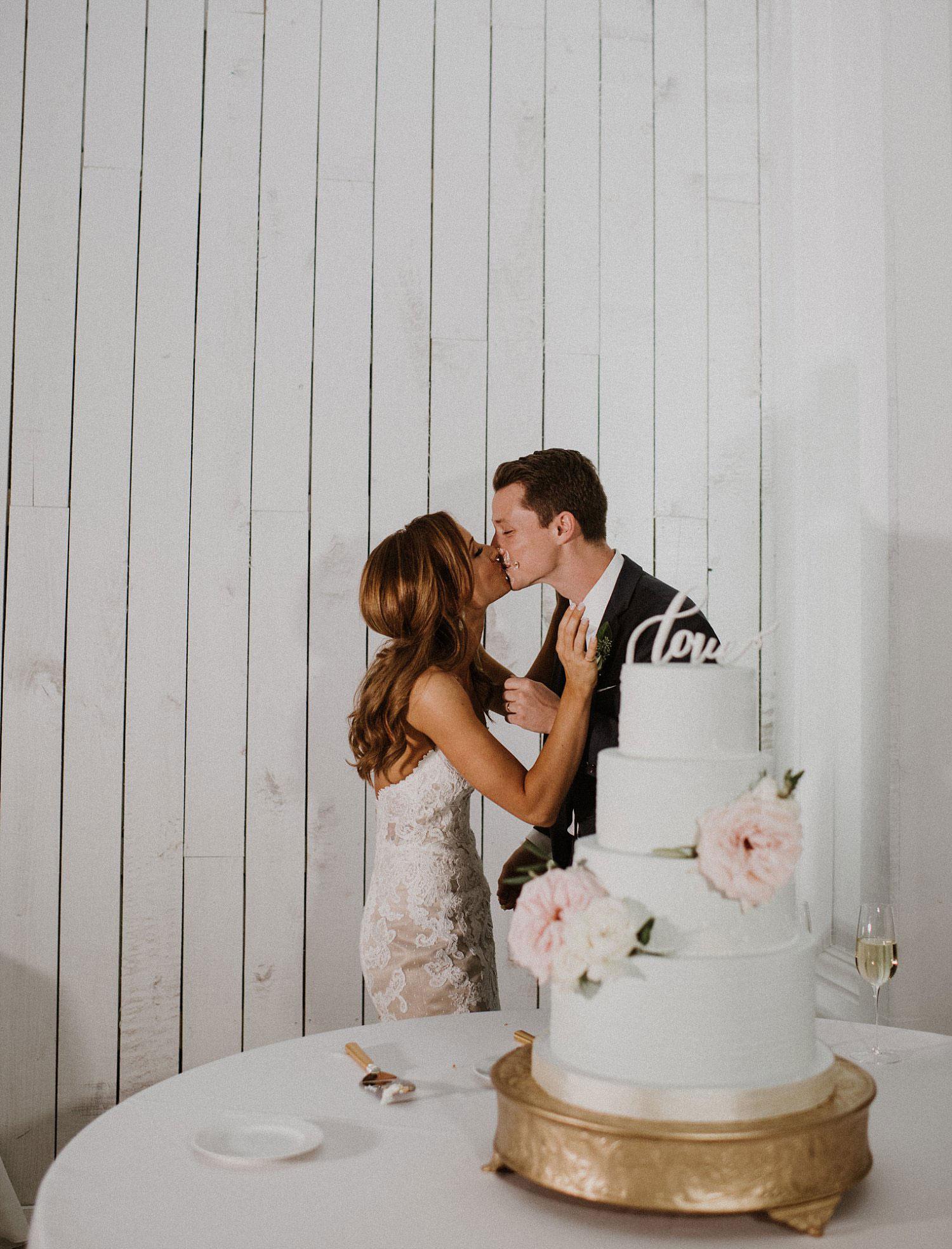 Bride and groom cutting wedding cake at white sparrow barn wedding