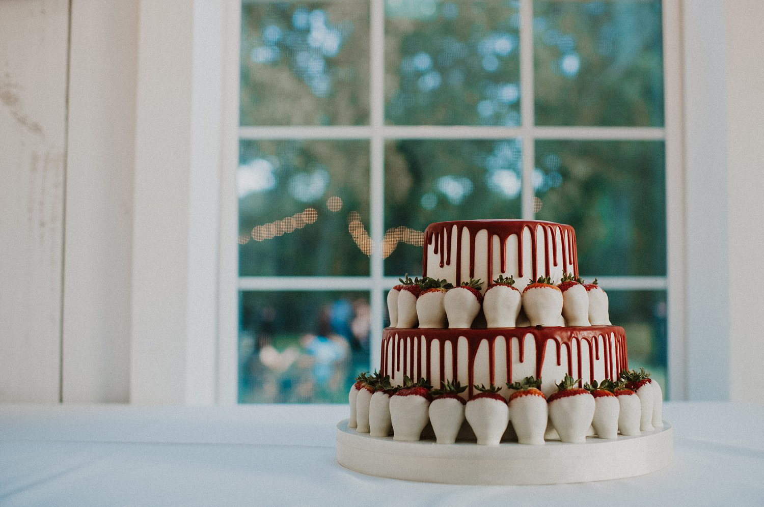 White and red groom drip cake with white chocolate strawberries