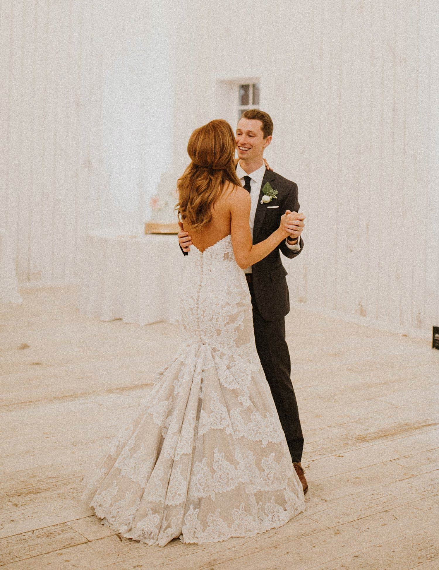 Bride wearing nude and lace dress while dancing with groom