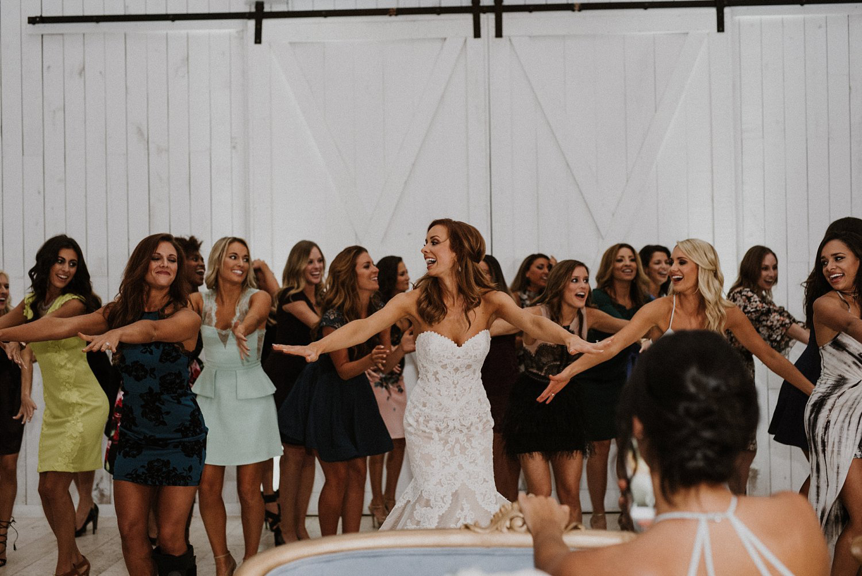 Dallas cowboy cheerleader bride dancing with cheerleaders at white sparrow barn wedding